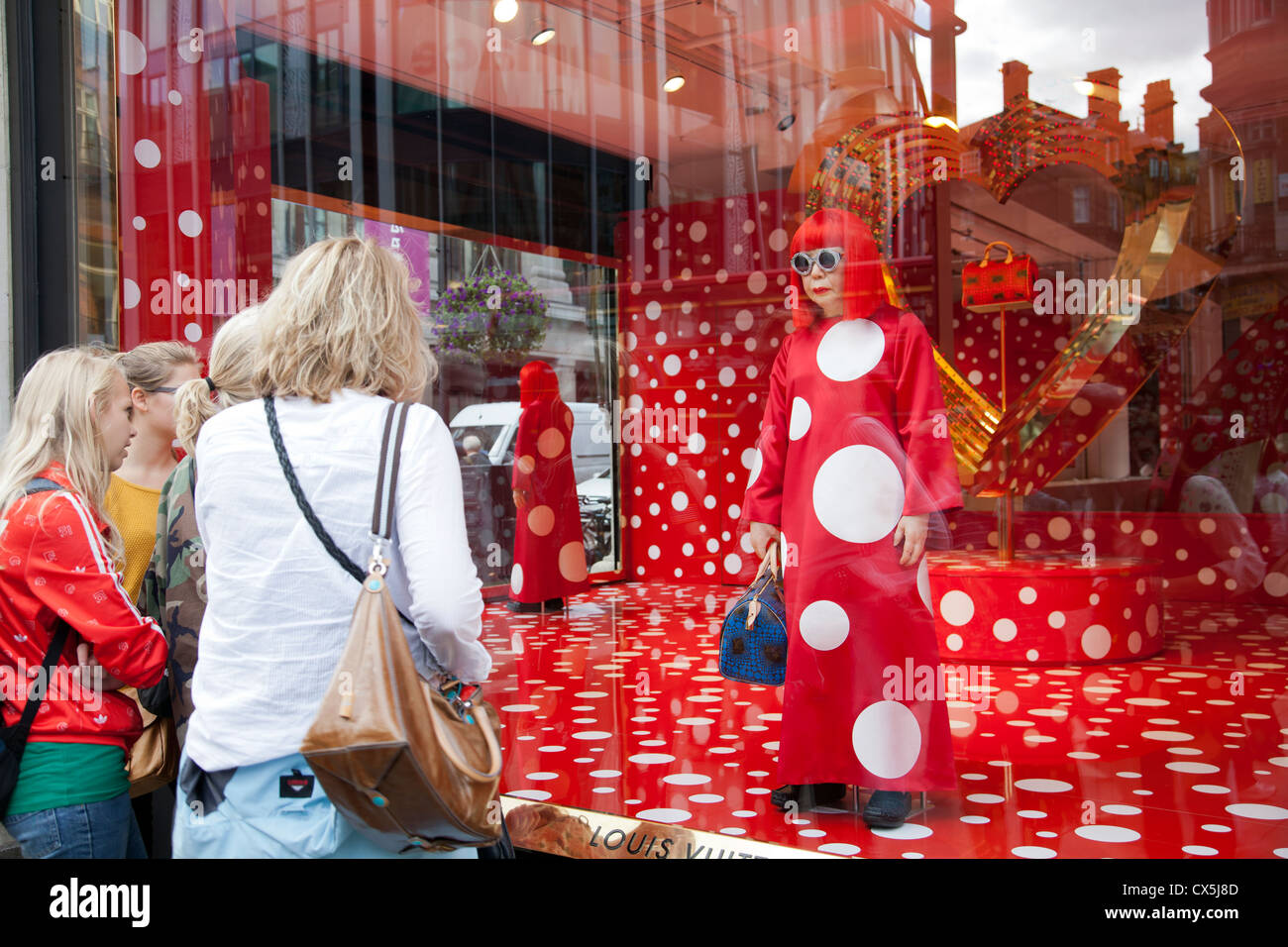38aa94fadbd Selfridges Joint window display between Louis Vuitton and artist Yayoi  Kusama - spectators look on - London UK