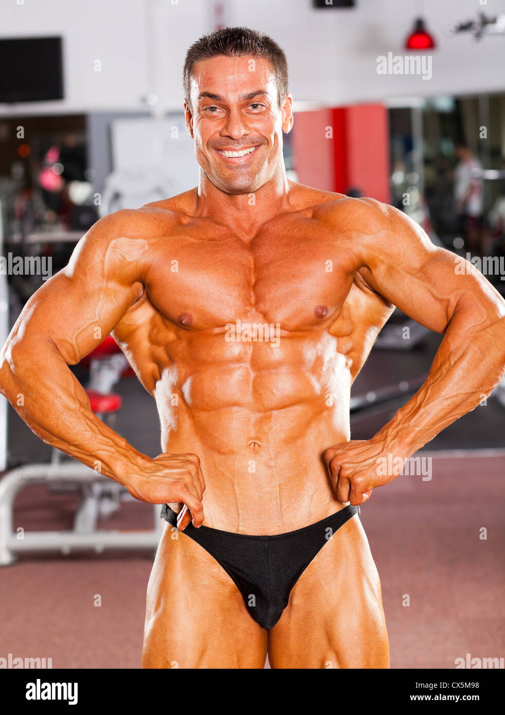 male bodybuilder flexing his muscle in gym - Stock Image