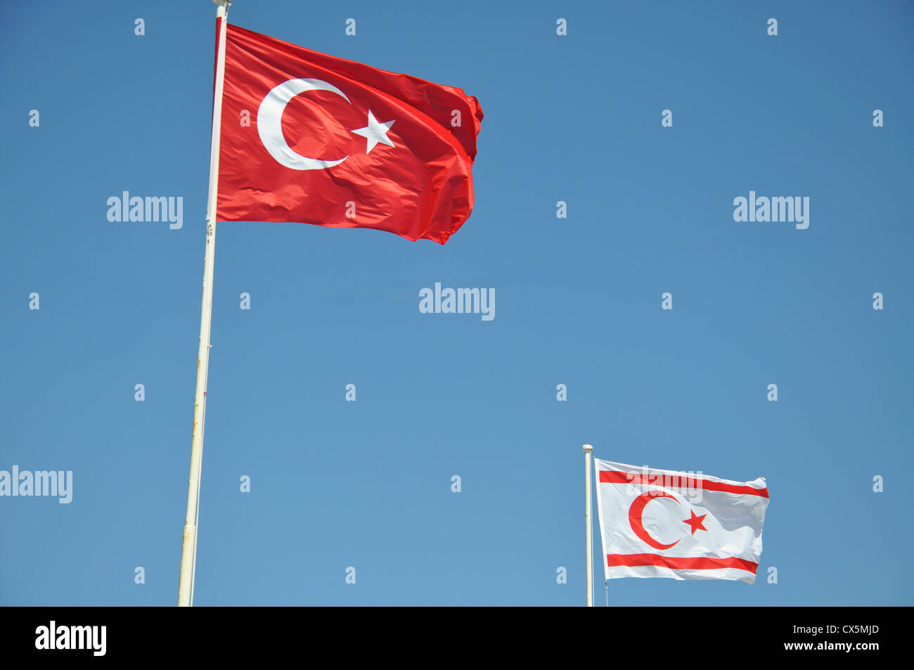 Turkish and Turkish Republic of Northern Cyprus Flag flying against a blue sky - Stock Image