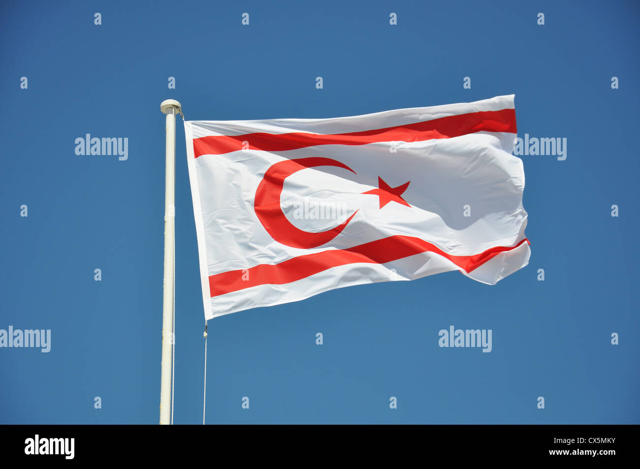 Turkish Republic Of Northern Cyprus (TRNC) flag flying against a blue sky - Stock Image