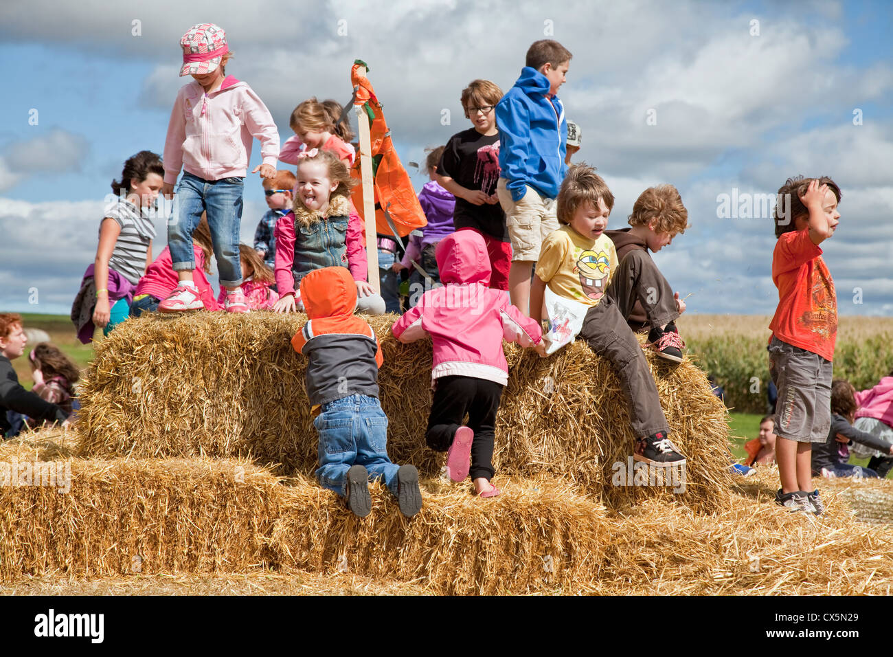 Children climbing and playing on a hay bale mountain at  the annual Scarecrow Festival held in Summerside, Prince - Stock Image