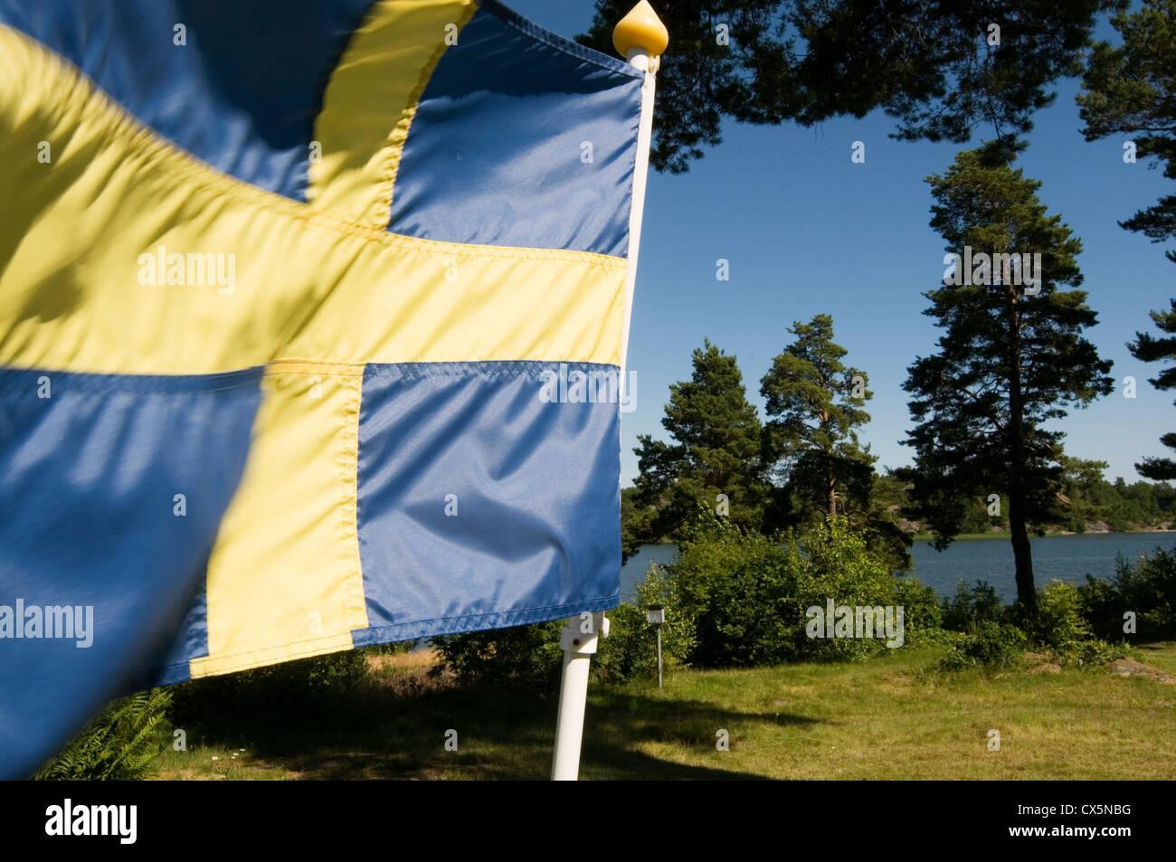 sweden swedish flag flags fluttering forest forests lake lakes countryside svenska svensk - Stock Image