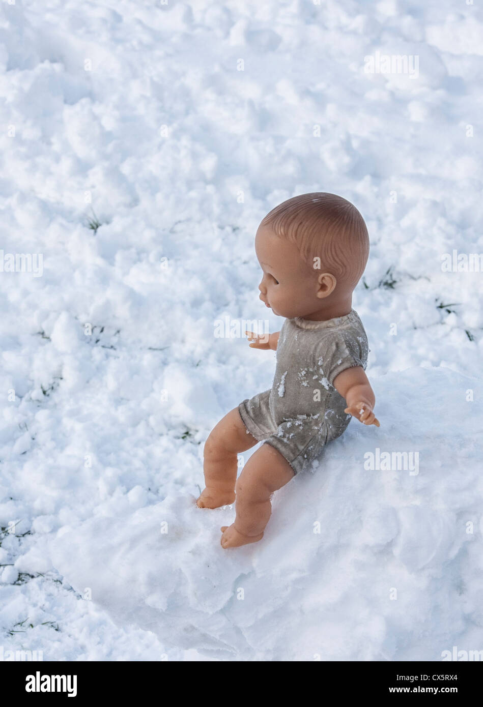 Lost or forgotten? A Doll in the Snow in a local park - Stock Image