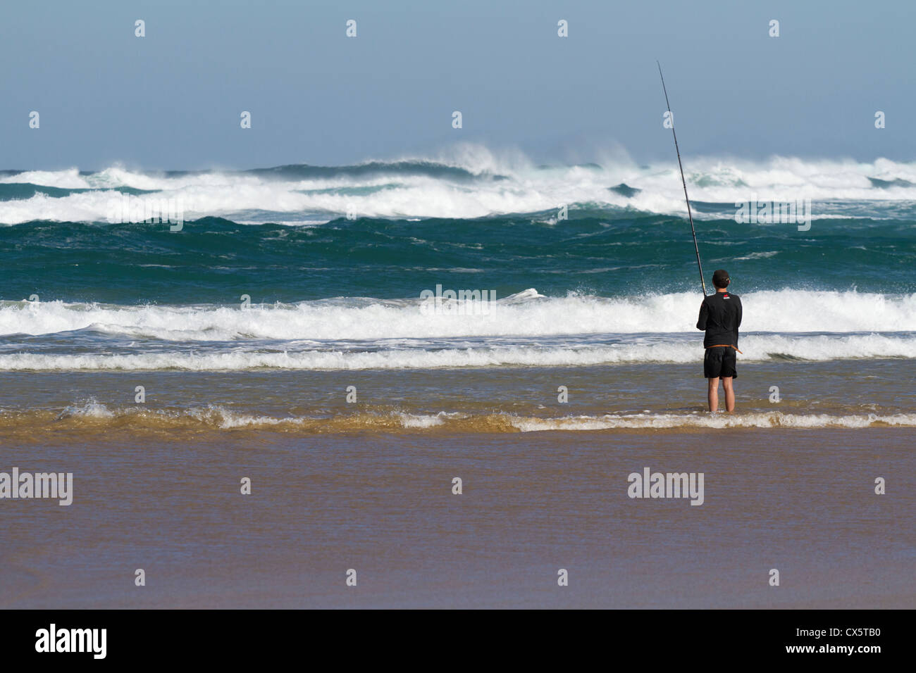 young man fishing from the beach in black shorts and tracksuit top looking away to rough choppy sea's with blue - Stock Image