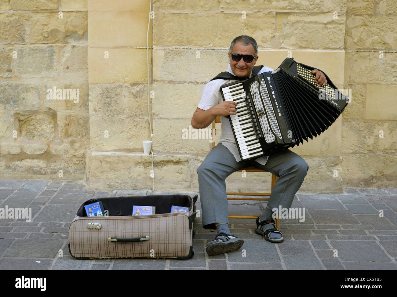 Street entertainer busker in Valetta, Malta playing the accordion. - Stock Image