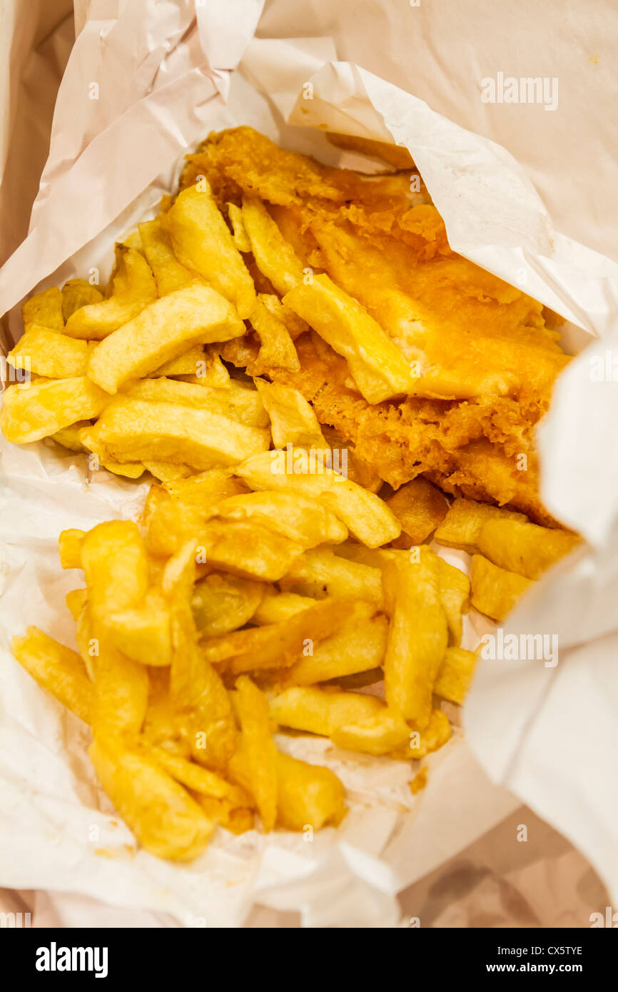 traditionally fried fish and chips wrapped in paper ready to be served - Stock Image