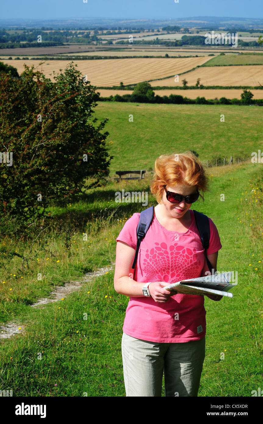 Woman looking at a map in the countryside near the Ridgeway, Chilterns, Oxfordshire, UK - Stock Image