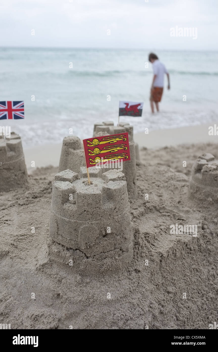 A child's sand castles with Scottish flag  in the foreground with welsh and union jack flags looking on from behind Stock Photo
