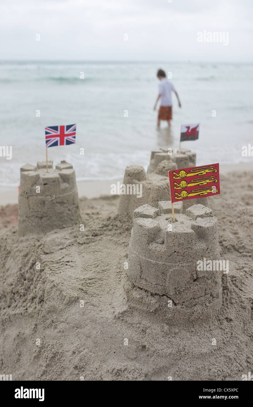 sandcastles with British flags in on a beach on a overcast day with the Scottish flag in the foreground Stock Photo
