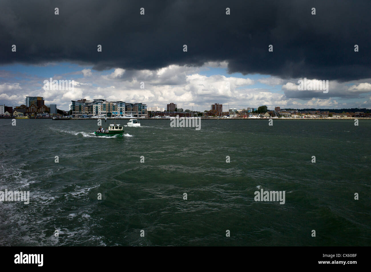 a weather storm black rain cloud approaches over Poole while the sea boats are bathed in sunlight - Stock Image