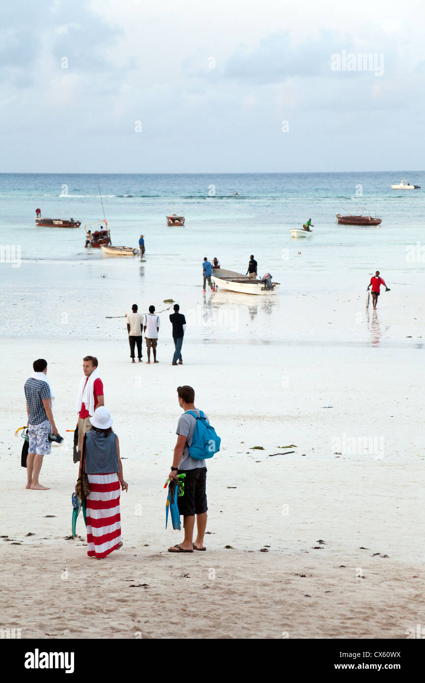Tourists and locals on the beach at Kizimkazi at dawn to go dolphin watching and swimming with dolphins, Zanzibar - Stock Image