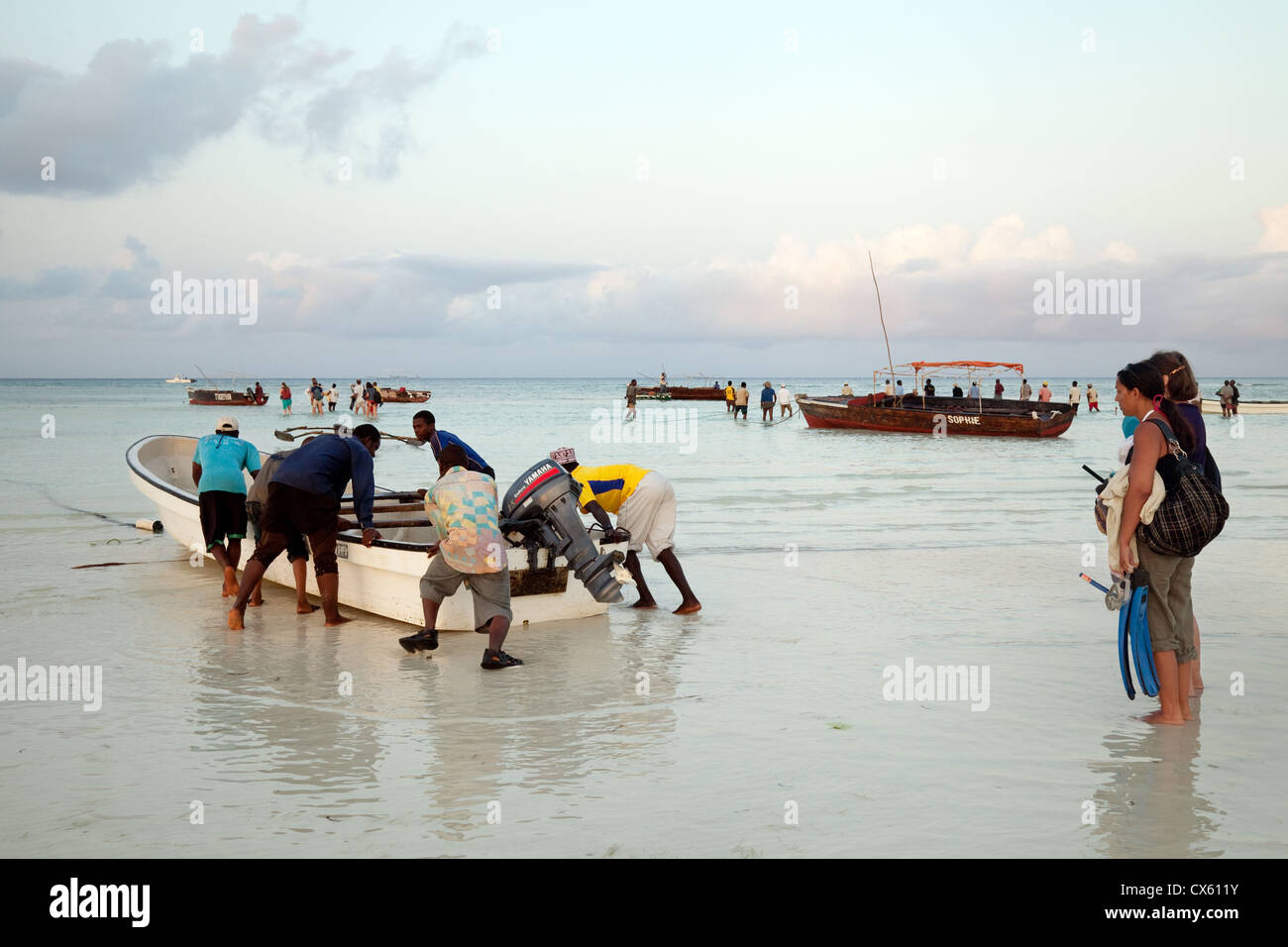 Tourists watching as their boat is pushed out for dolphin watching, Kizimkazi beach, Zanzibar Africa - Stock Image