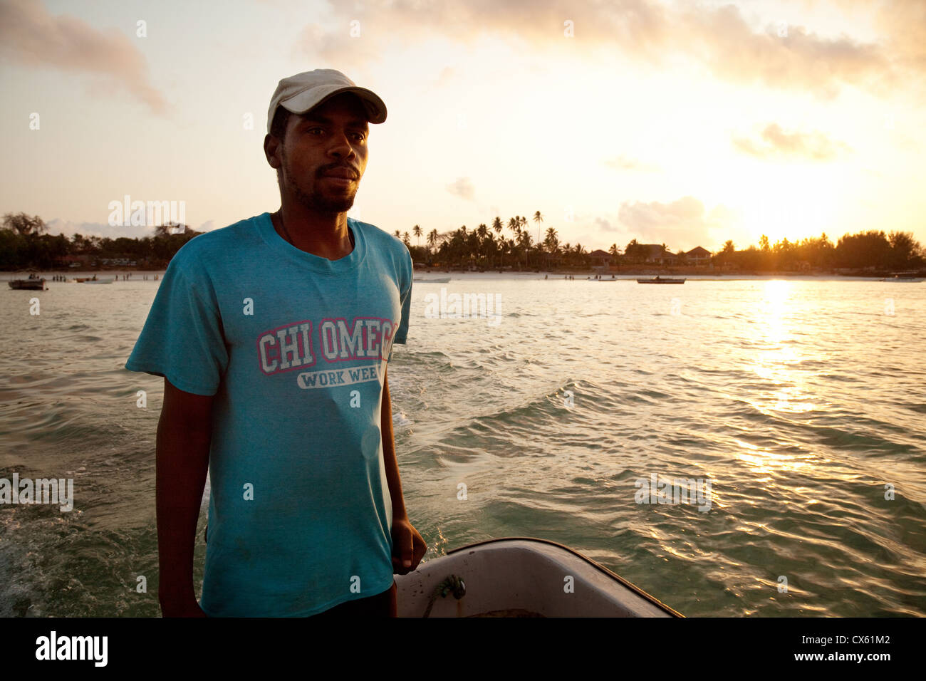 A Zanzibari african man steering his boat on the Indian Ocean at sunrise to go dolphin watching, Zanzibar Africa - Stock Image