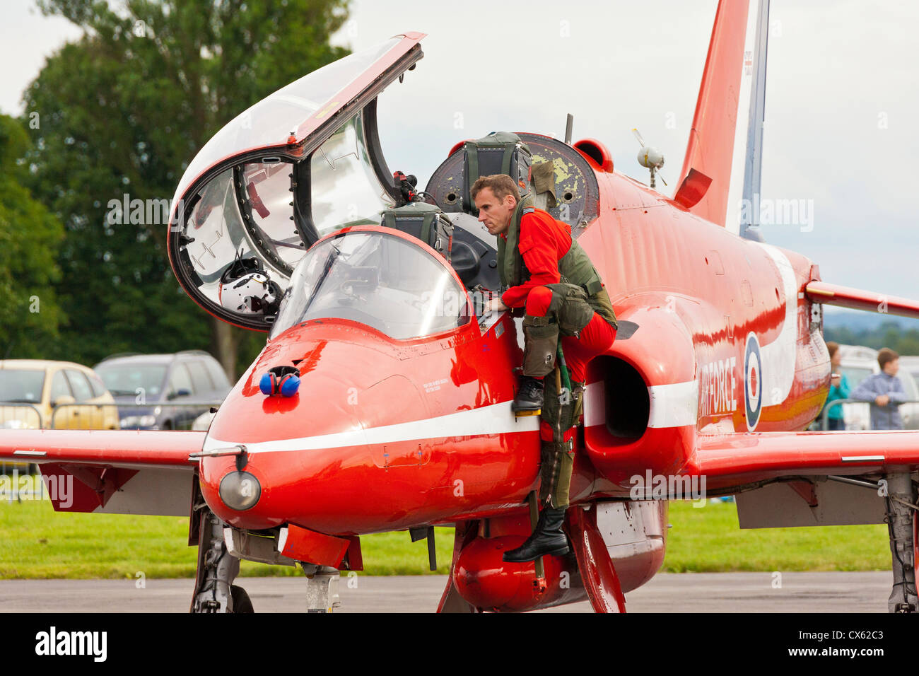 RAF Red Arrows Hawk pilot climbs out of his aircraft at Kemble Airport after the aerobatic display has ended. JMH6098 - Stock Image