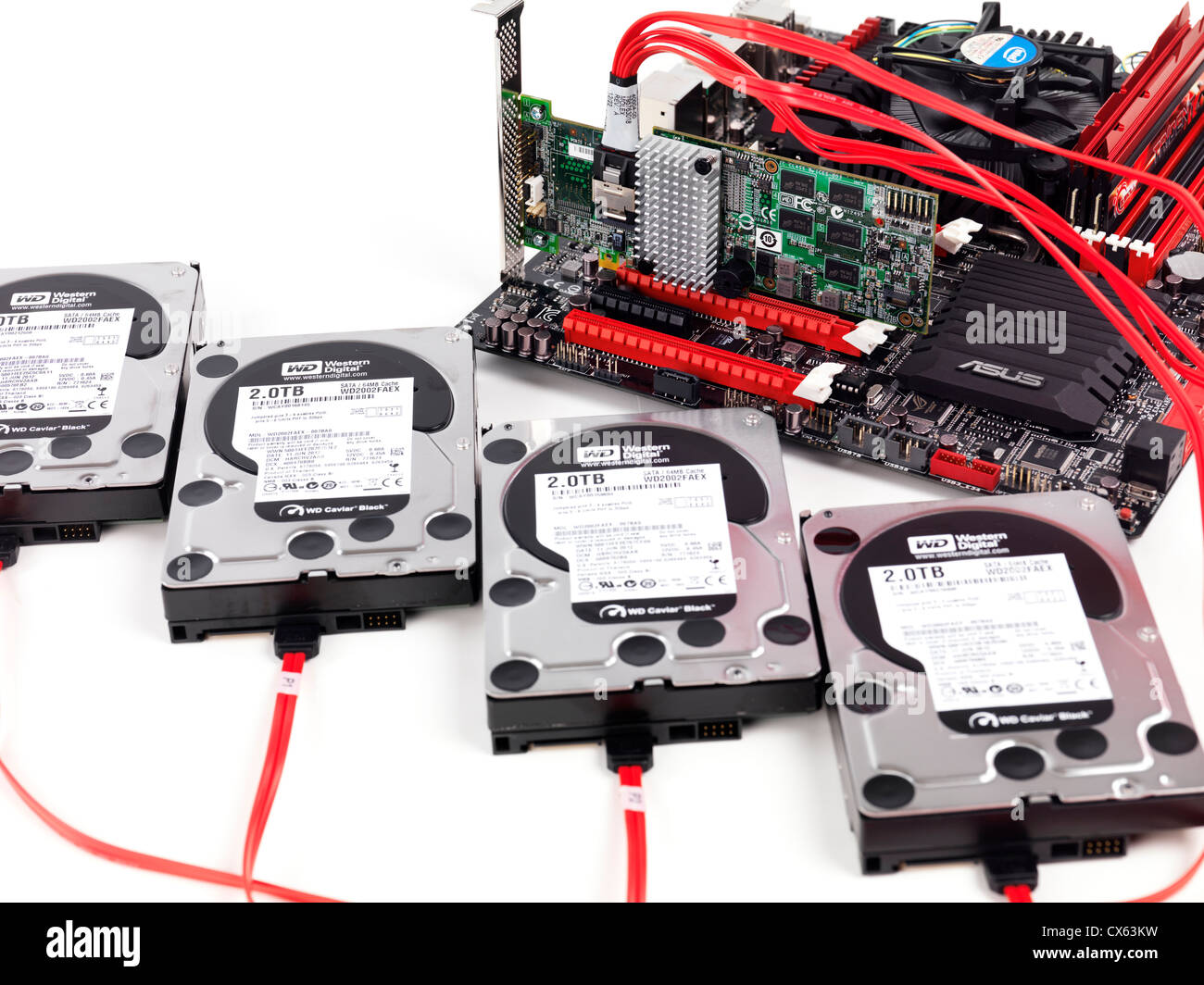 Closeup of four hard drives connected to computer motherboard with a RAID controller - Stock Image