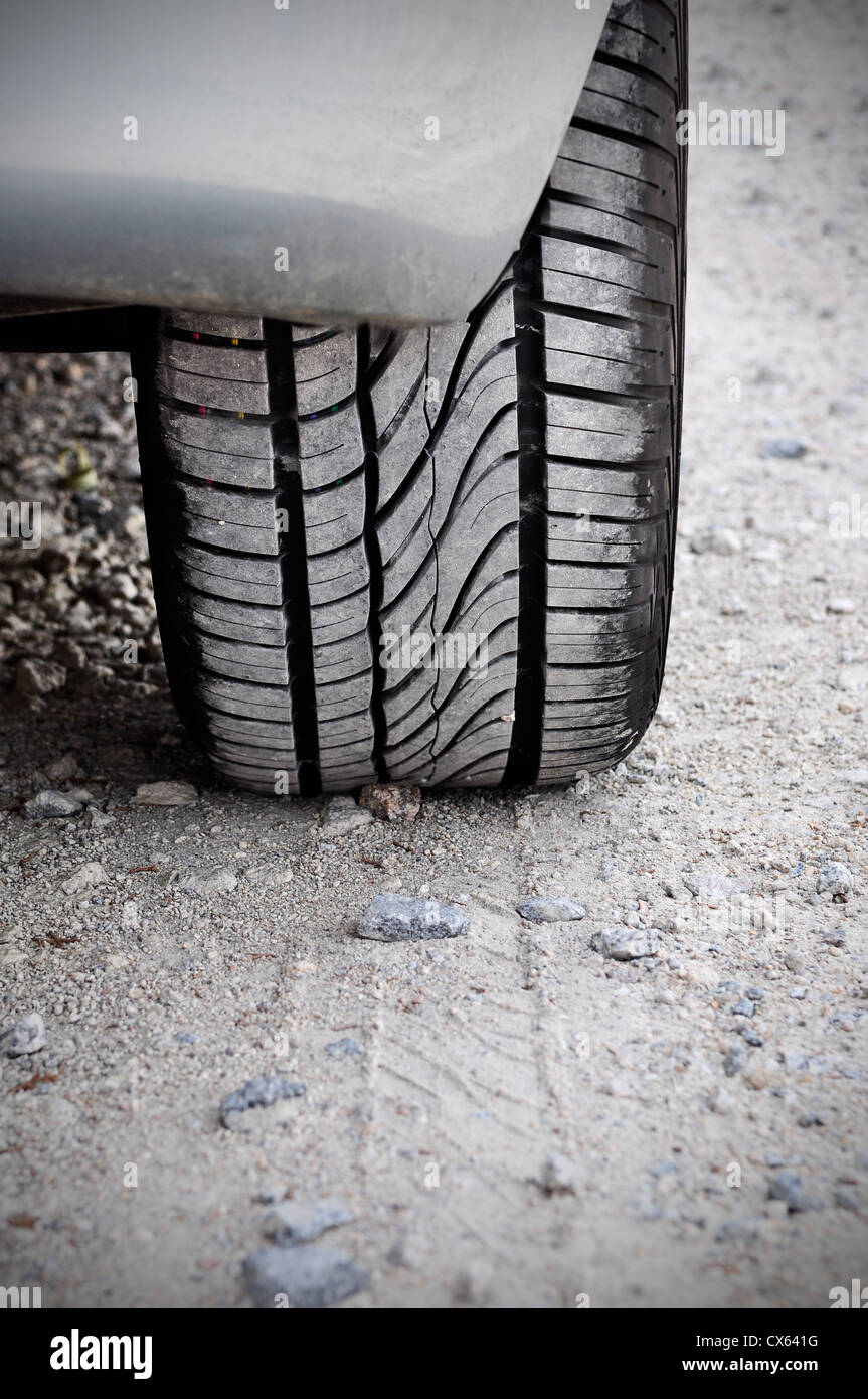 Close up of a car tire on a dirty road. Gritty look and vignetting on the corners of the image - Stock Image