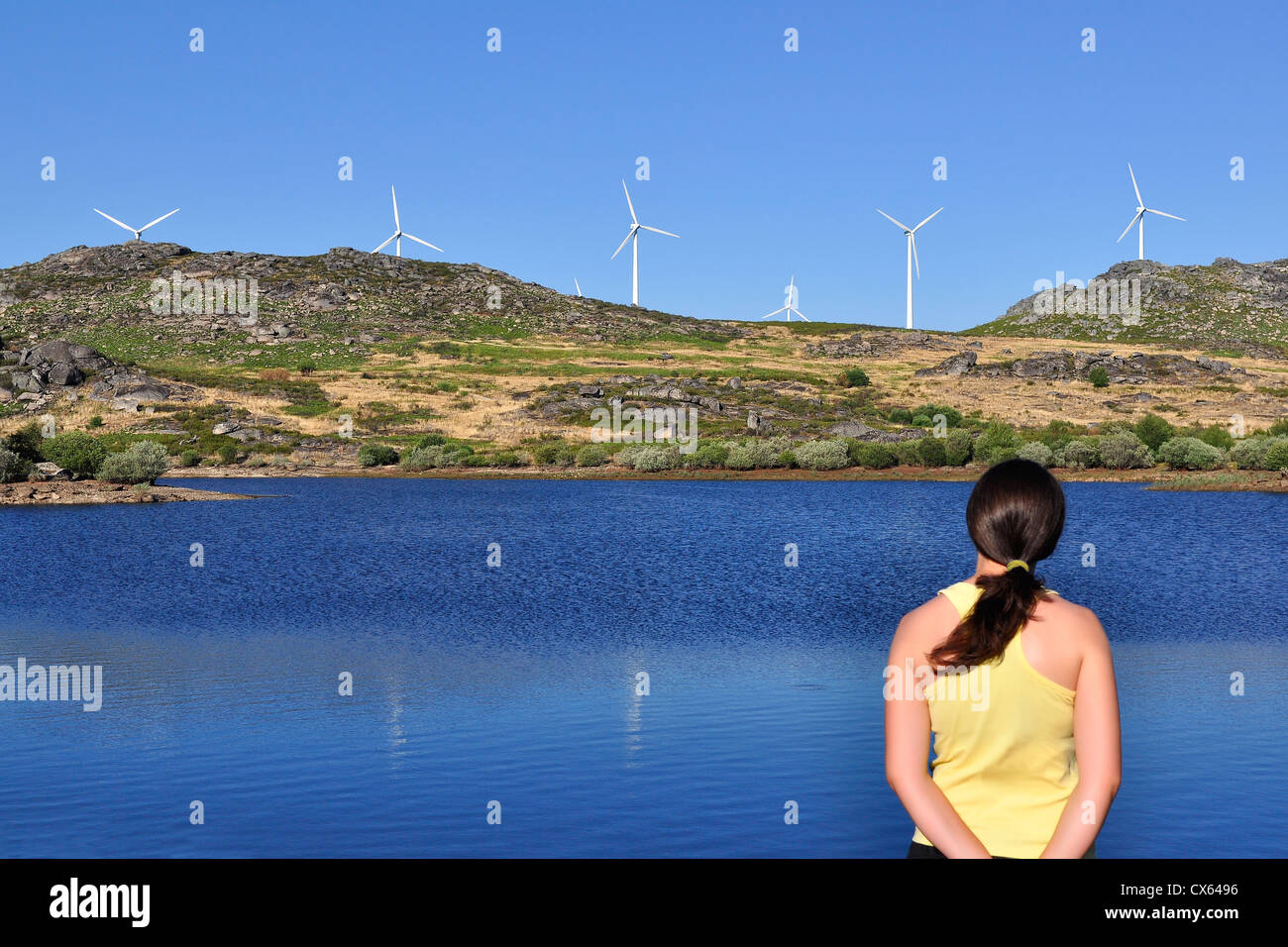 Woman looking at a wind mill across a lake. Focus is on the wind turbines and the woman is slightly out of focus. - Stock Image