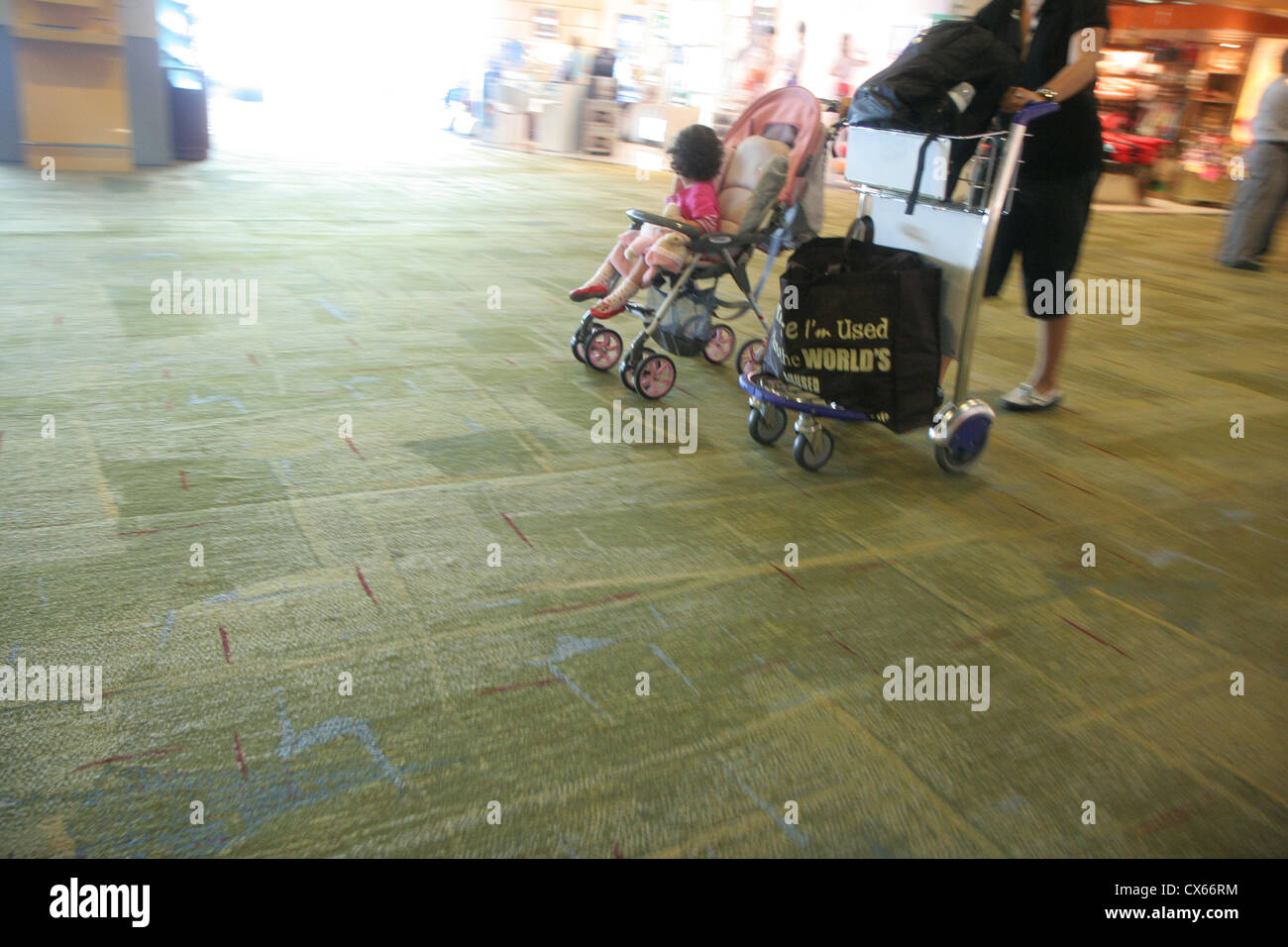 Woman push a toddler cart and baggage cart simultaneously in Changi International Airport, Singapore. - Stock Image