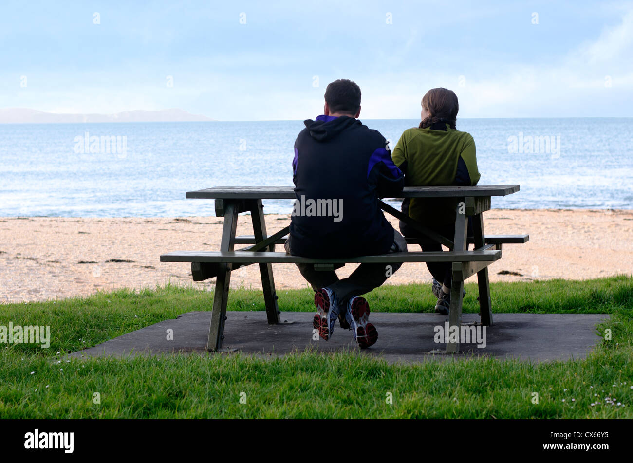 Man and woman sitting on opposite sides of park bench. Copy space above with room for text. - Stock Image