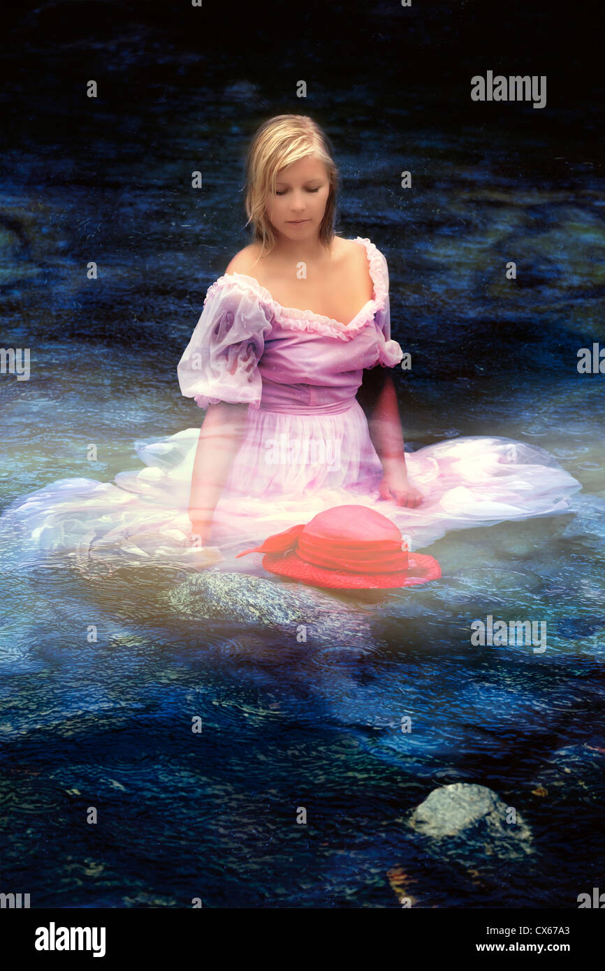 a woman in a gown is sitting in water - Stock Image