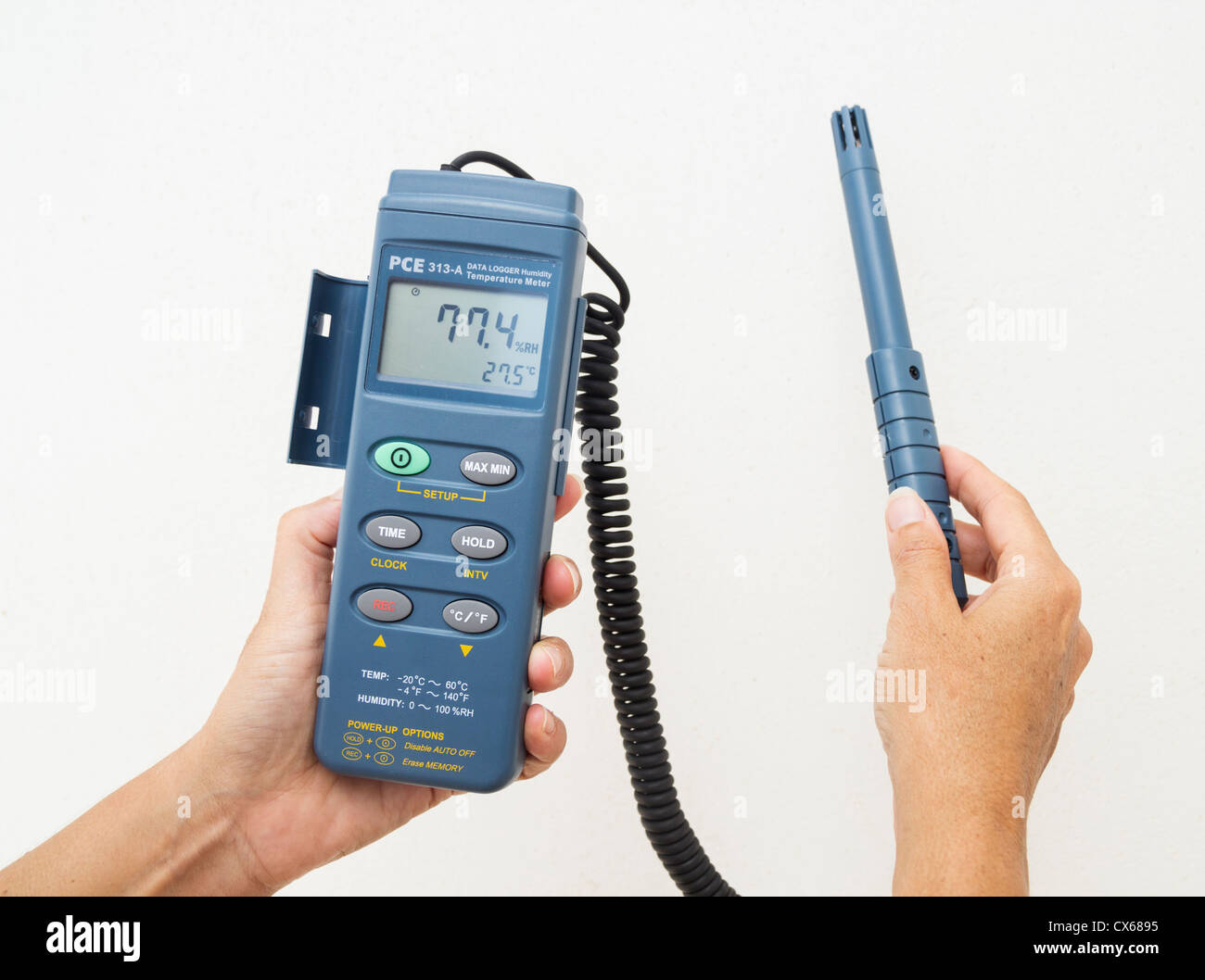 Female technical architect holding hygrometer, device for measuring humidity, against white external wall - Stock Image