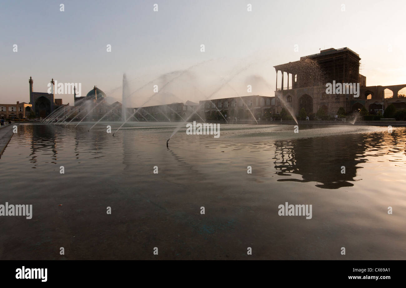 Fountain with sight of the Imam mosque and the Ali Qapu palace on the Naqsh-e Jahan Square, or Imam square, in Isfahan, Stock Photo