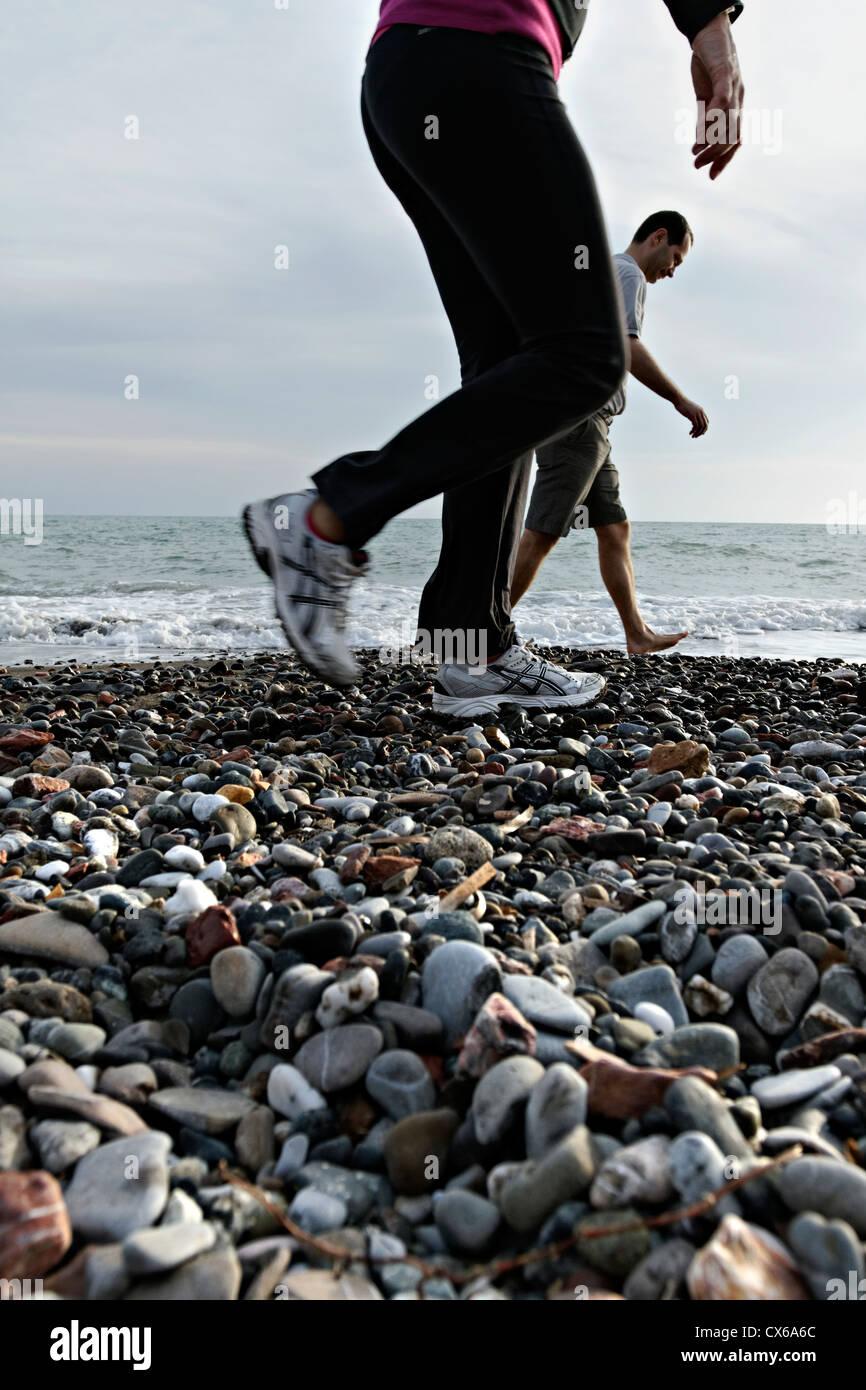 2 people walking on a stony beach, Cecina Mare Tuscany Italy - Stock Image