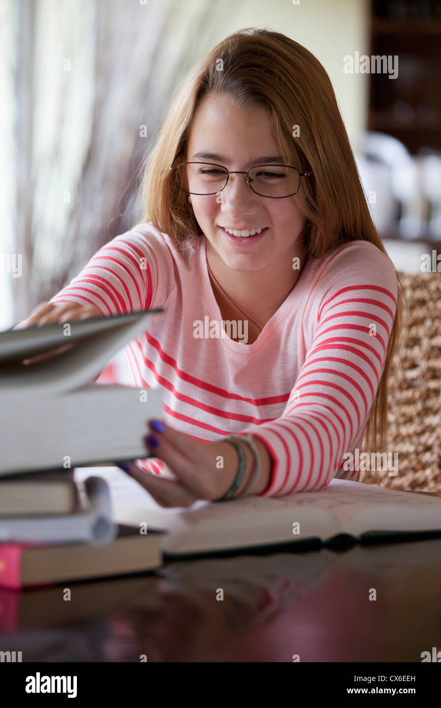 Busy girl grabs book - Stock Image