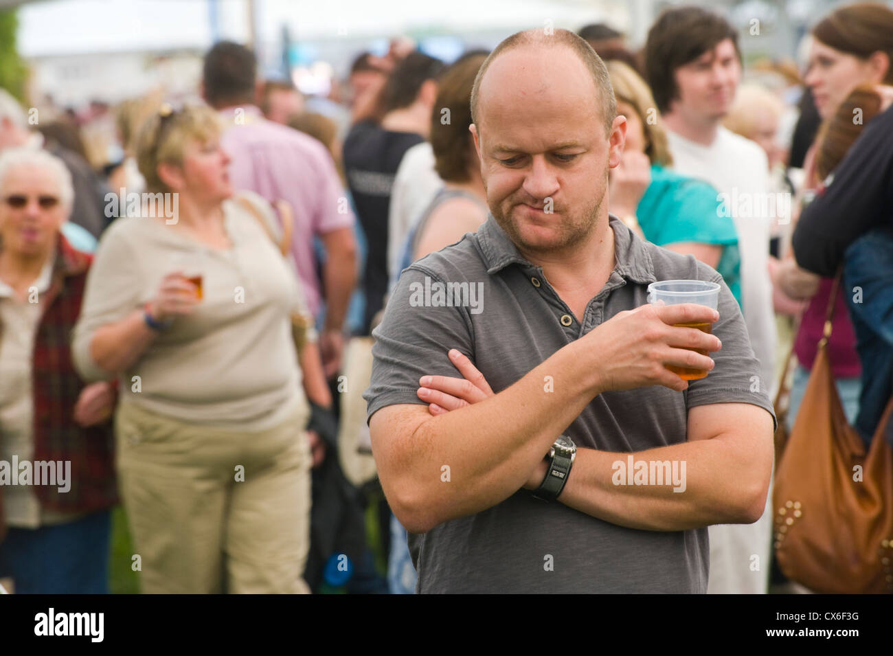 Man drinking beer in crowd at Ludlow Food Festival 2012 Ludlow Shropshire England UK - Stock Image