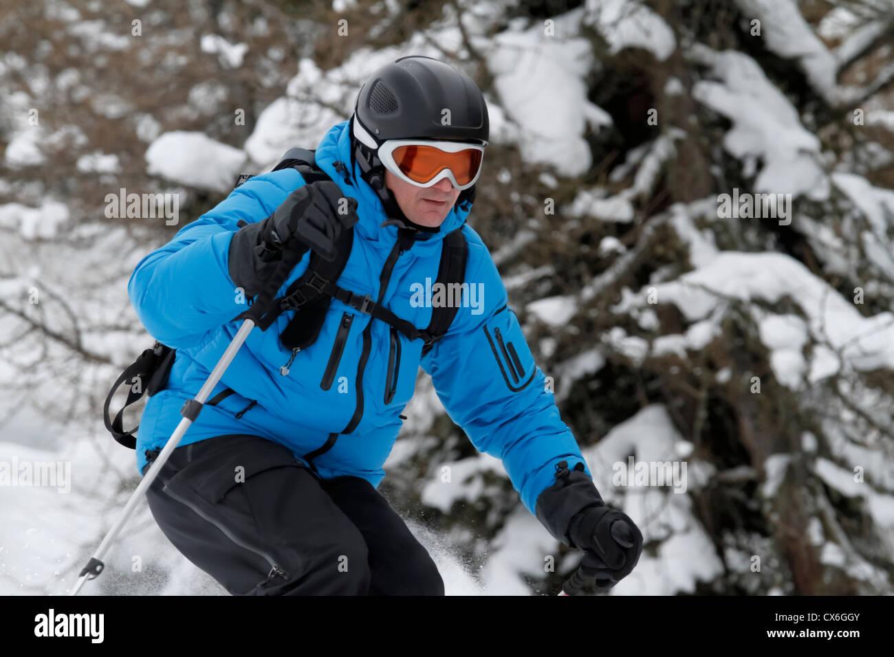 Skier is freeriding between trees - Stock Image