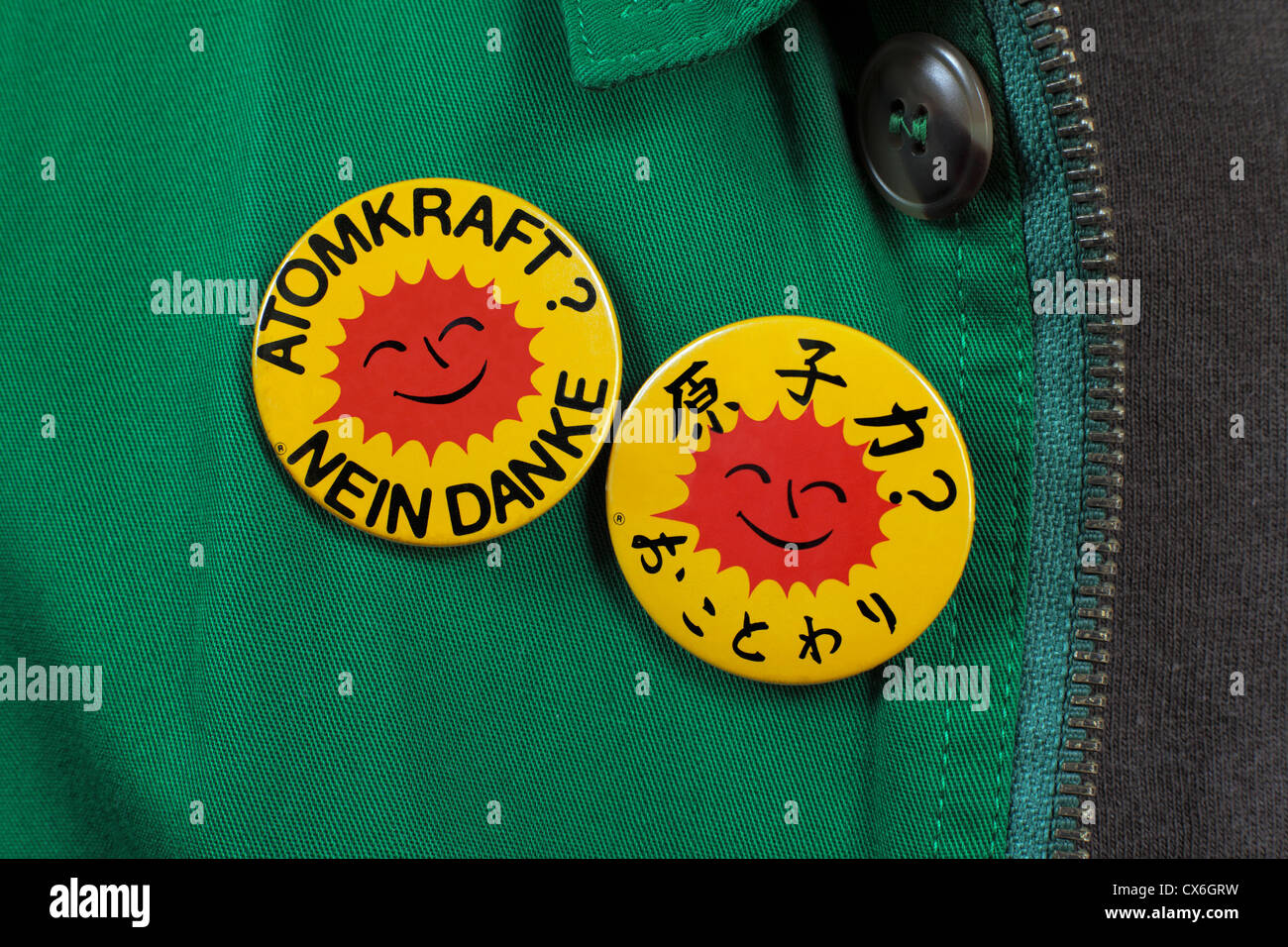 Person wearing two anti-nuclear power badges, reading 'Nuclear Power? No Thanks' in German and Japanese. - Stock Image