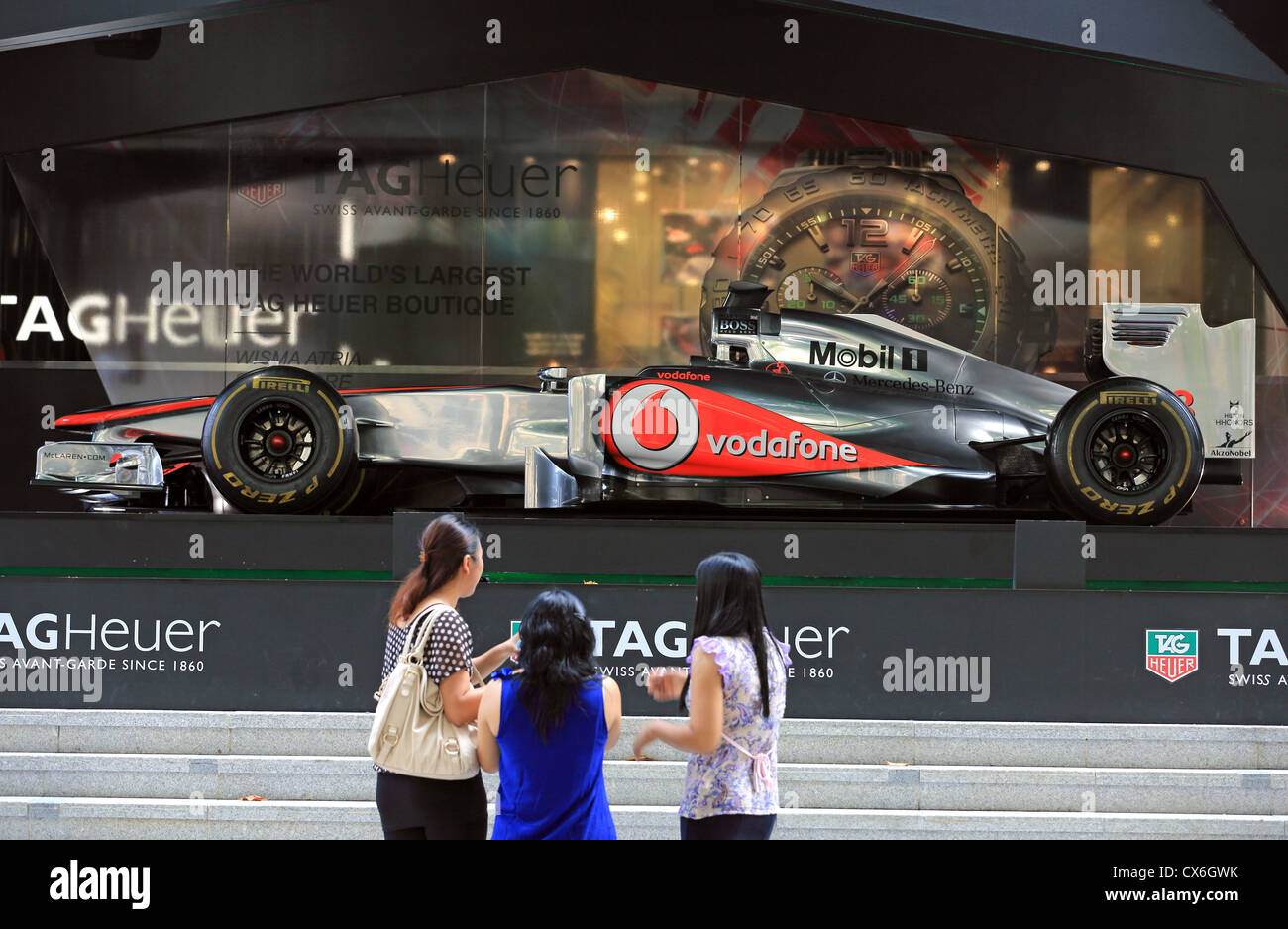 Woman admiring Jenson Button's McLaren Mercedes Formula One racing car on display in Singapore before the Singapore - Stock Image