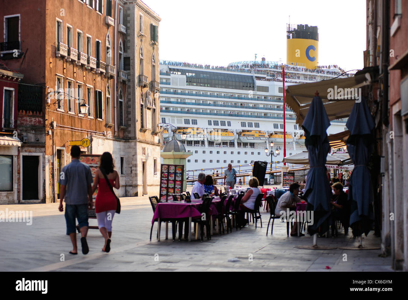 Big Cruise passing by Venice's seafront in front of tourists, Italy. - Stock Image