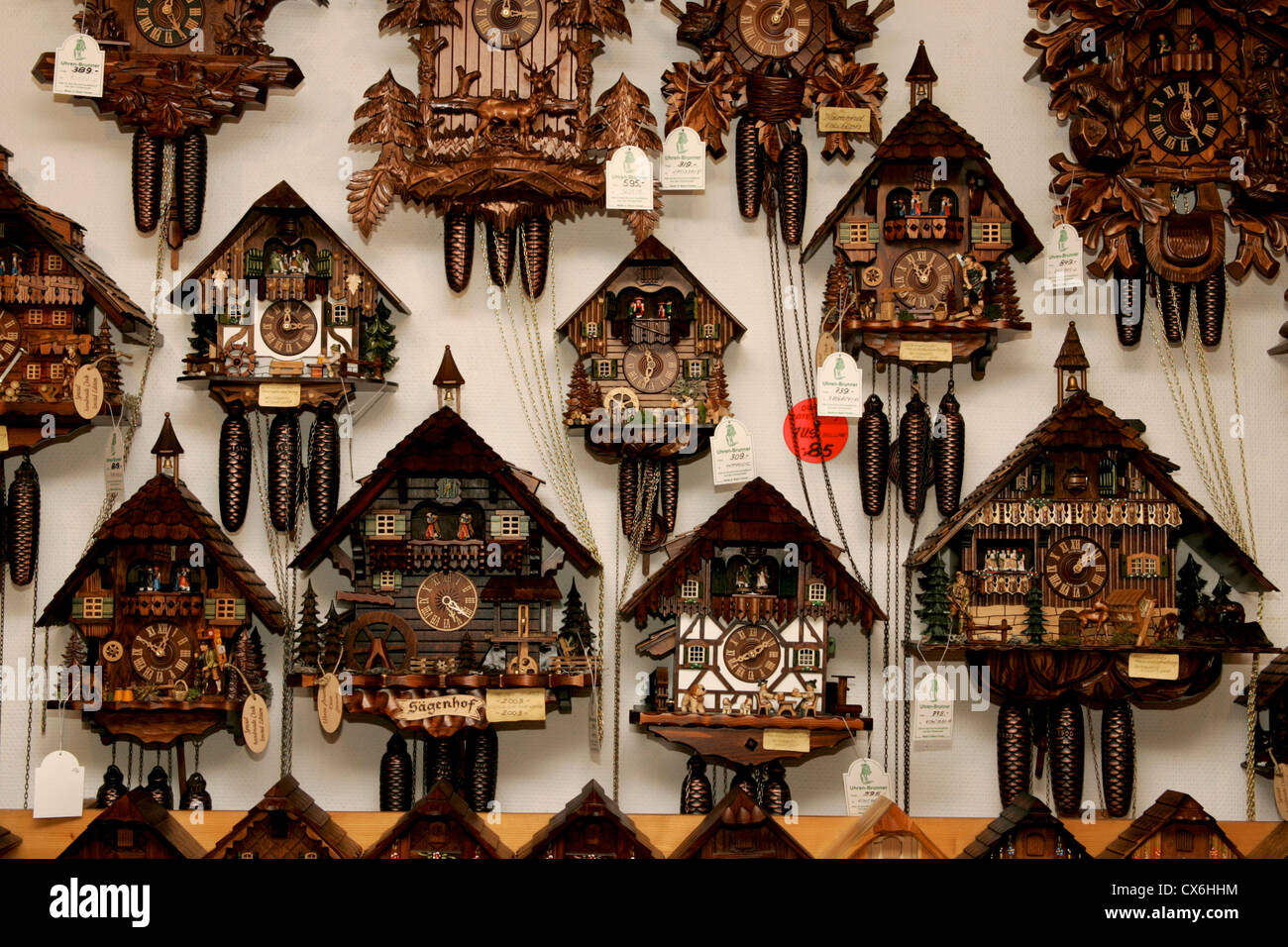 Several German Black Forest cuckoo clocks hanging on wall displayed, traditional craft from Bavaria village  Baden - Stock Image