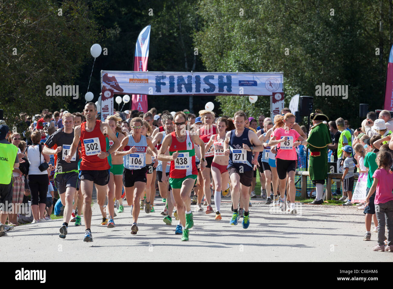 Runners starting the  10k and 5k run at Alice Holt Forest with Finish sign - Stock Image