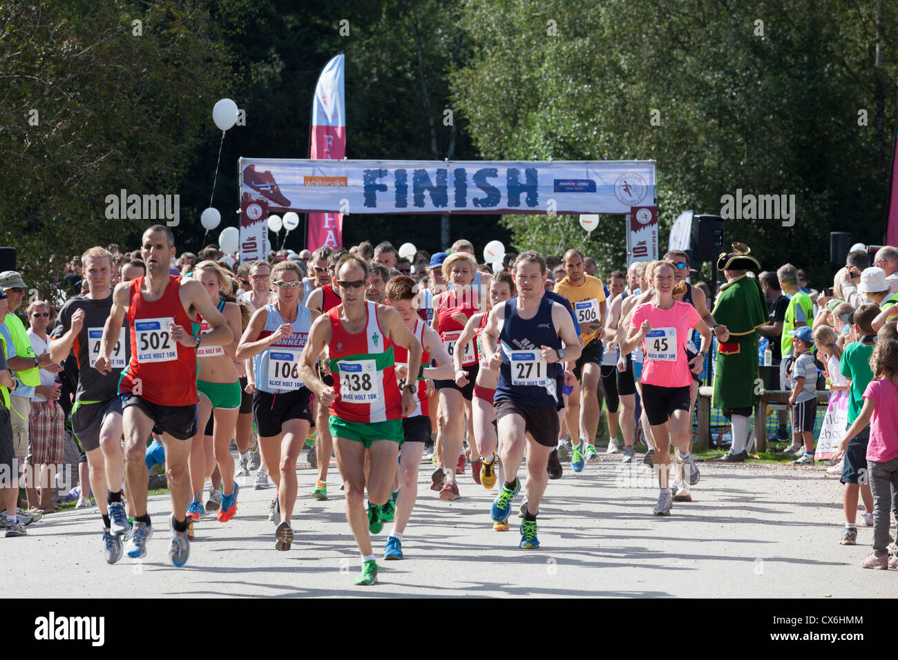 Runners starting the 10k and 5k run at Alice Holt Forest with Finish sign. - Stock Image