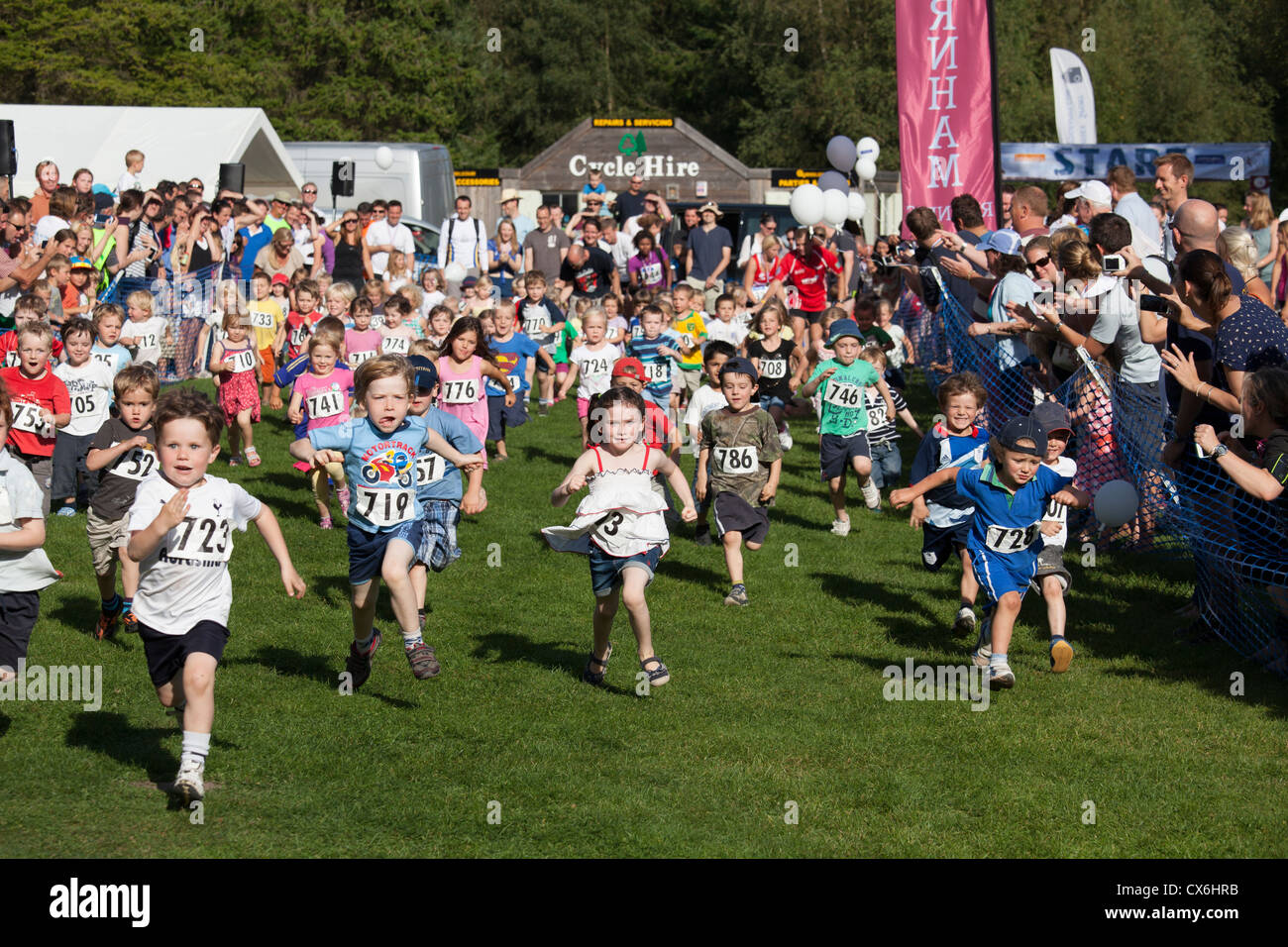 pre school children taking part in a 60m dash race with parents watching at Alice Holt Forest - Stock Image