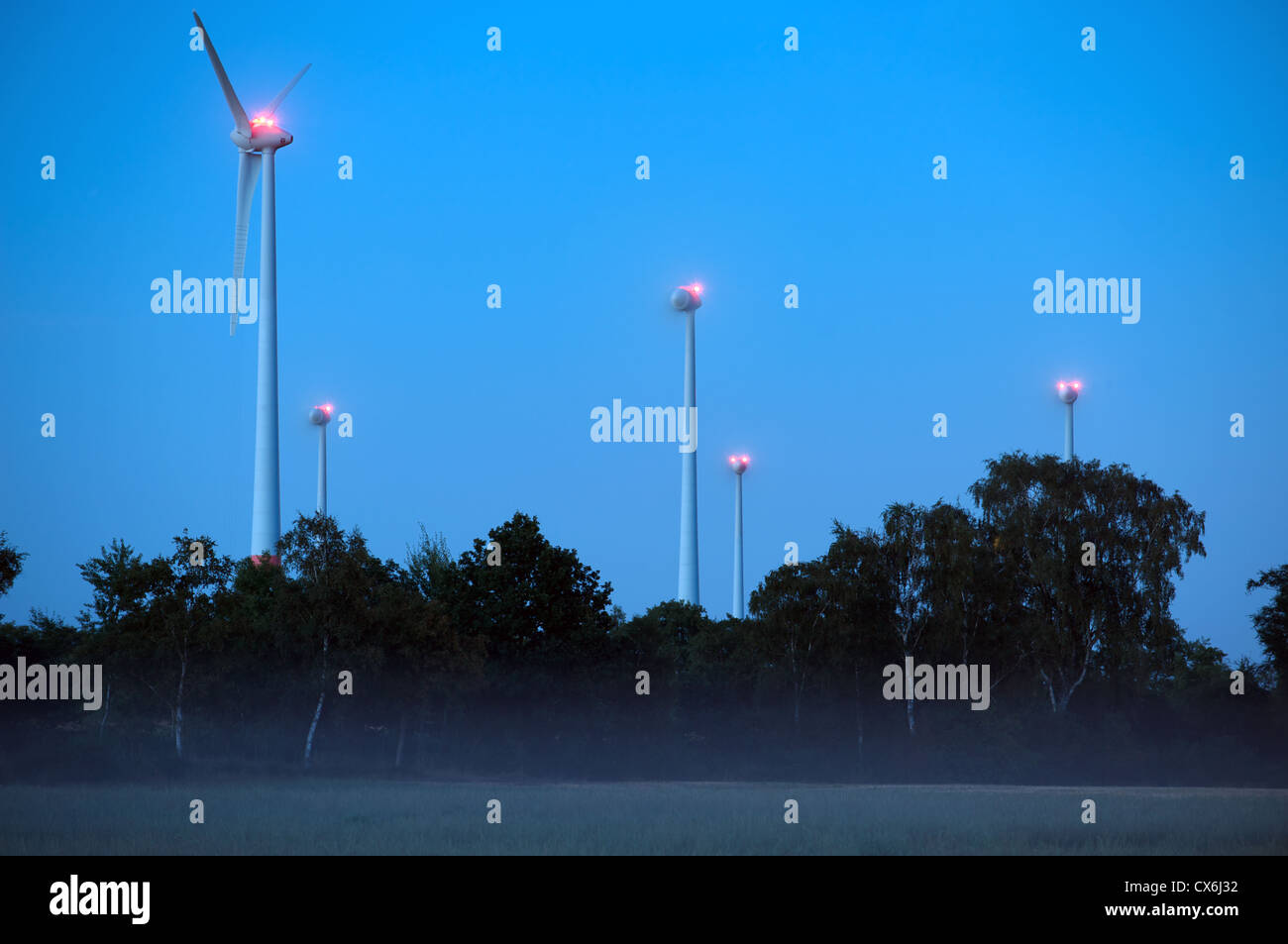 Windfarm at night consisting of German built Enercon E-40 turbines, one of which is under going maintenance and Stock Photo