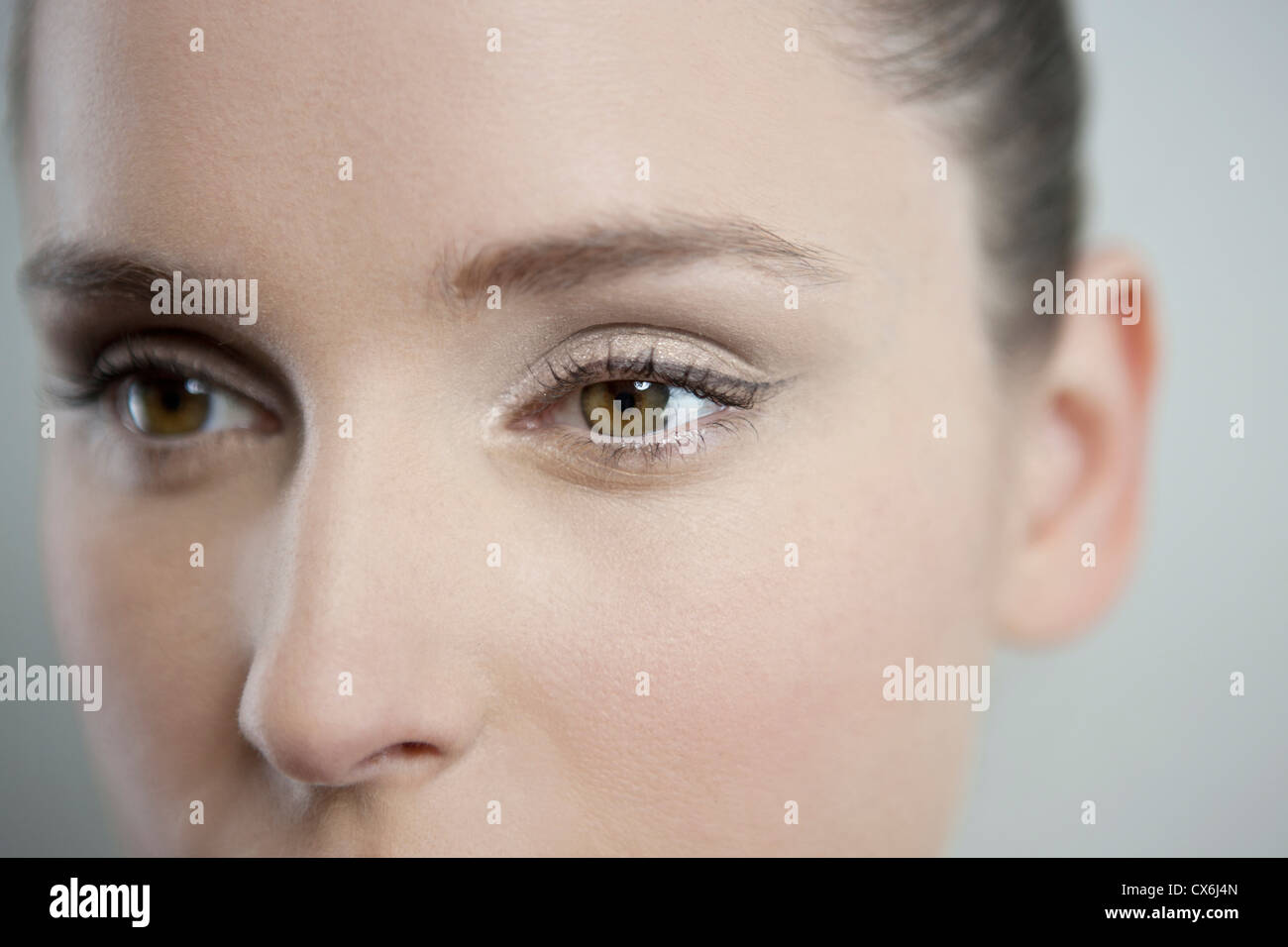 A young woman looking away, focus on left eye - Stock Image