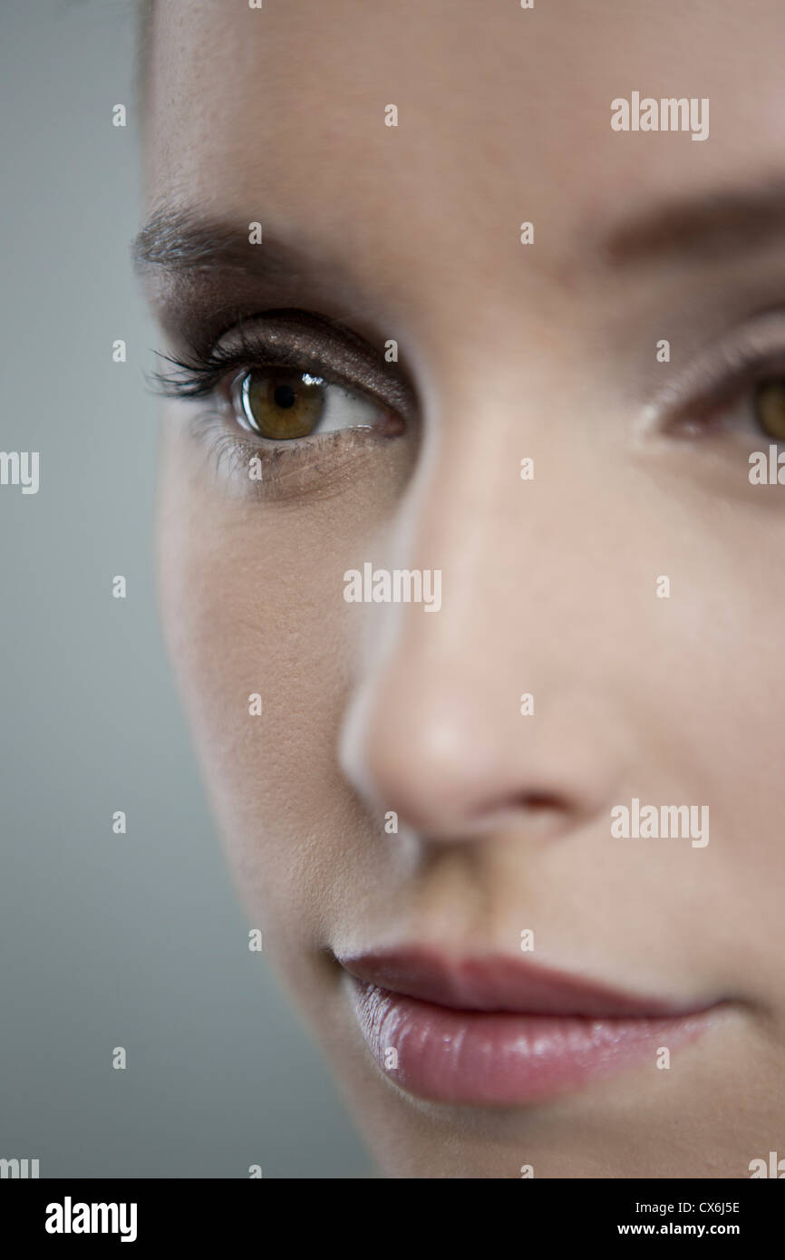 A young woman looking away, focus on right eye - Stock Image