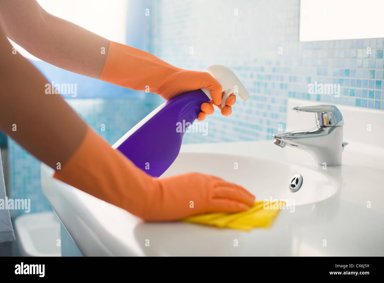 Woman Doing Chores In Bathroom At Home Cleaning Sink And Faucet - Bathroom detergent