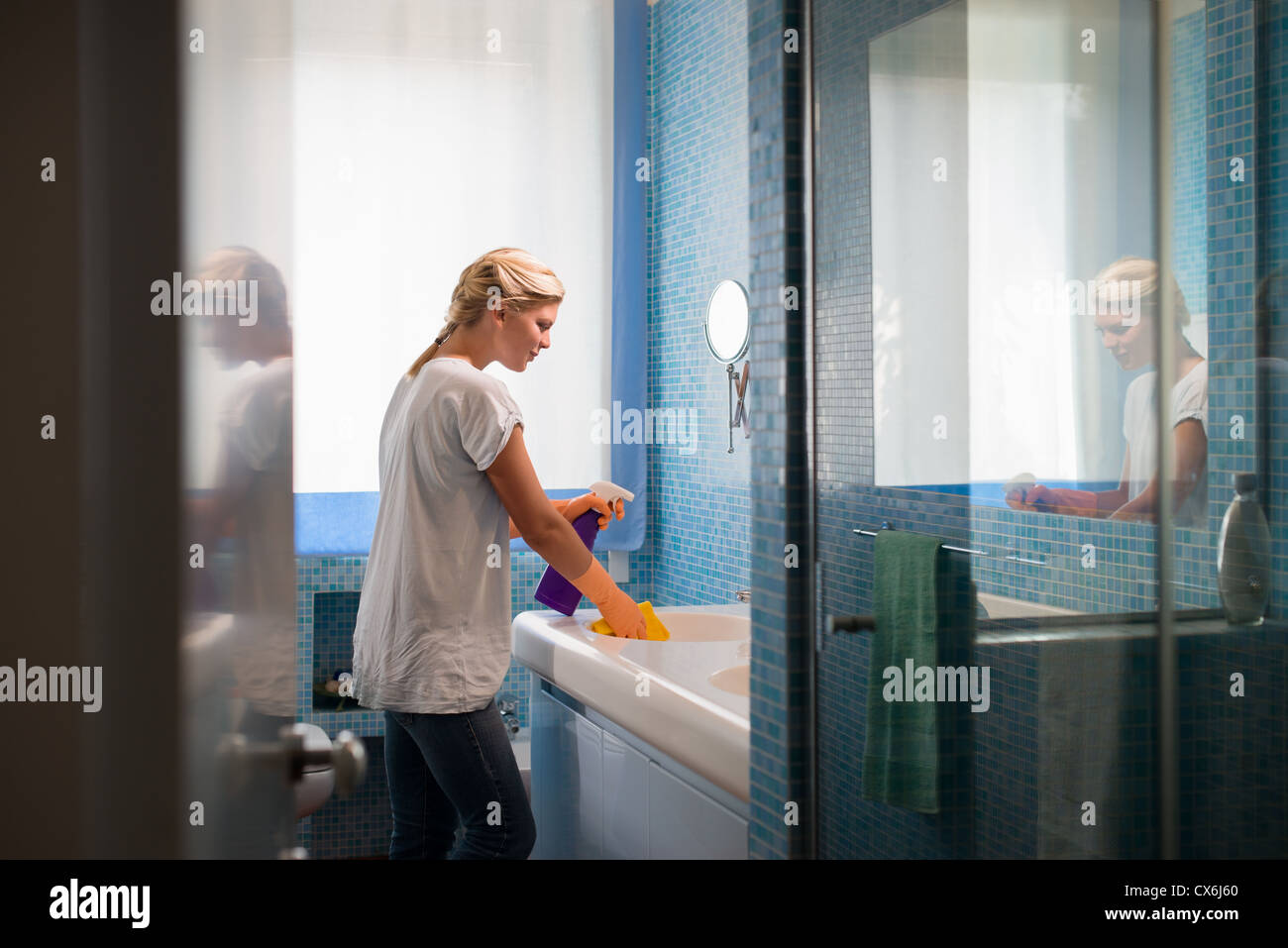 Housework and domestic lifestyle: woman doing chores in bathroom at home, cleaning wash basin and tap with spray - Stock Image