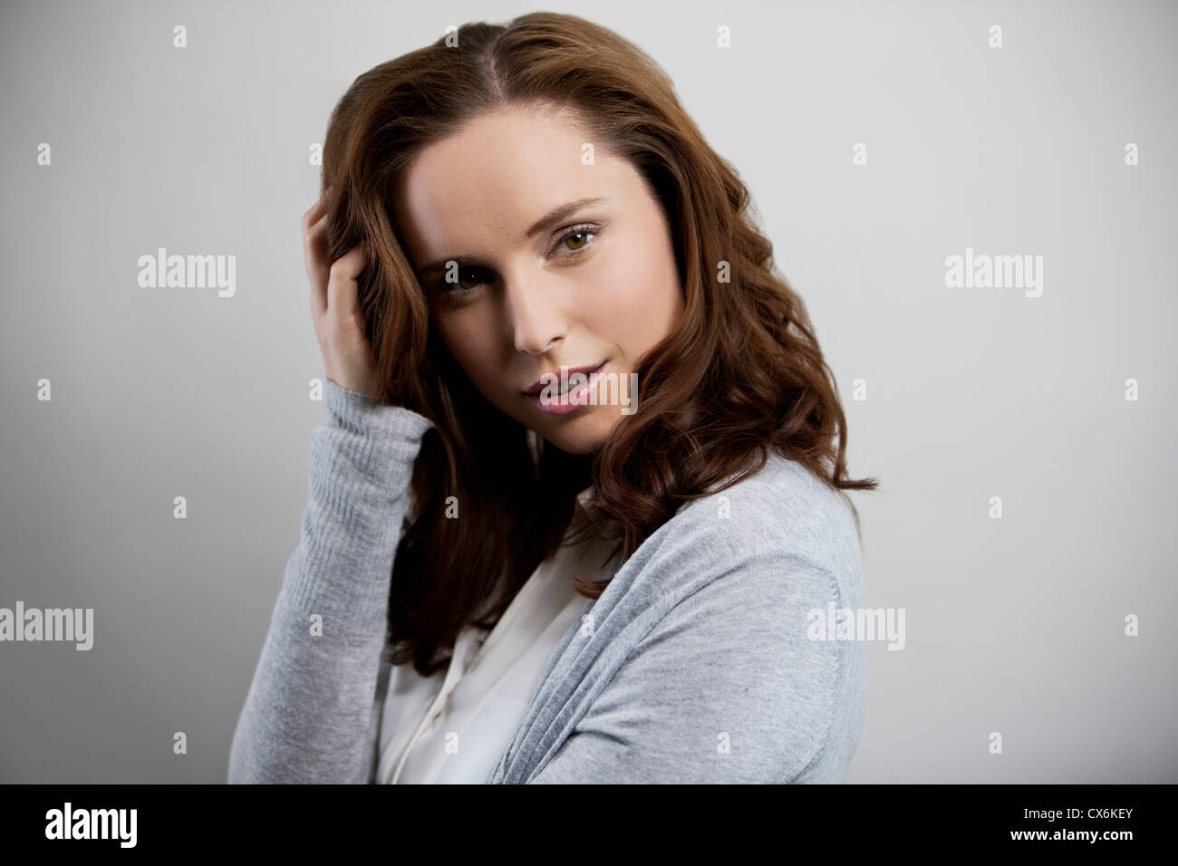 A young woman standing side on, looking to camera, hand to head - Stock Image