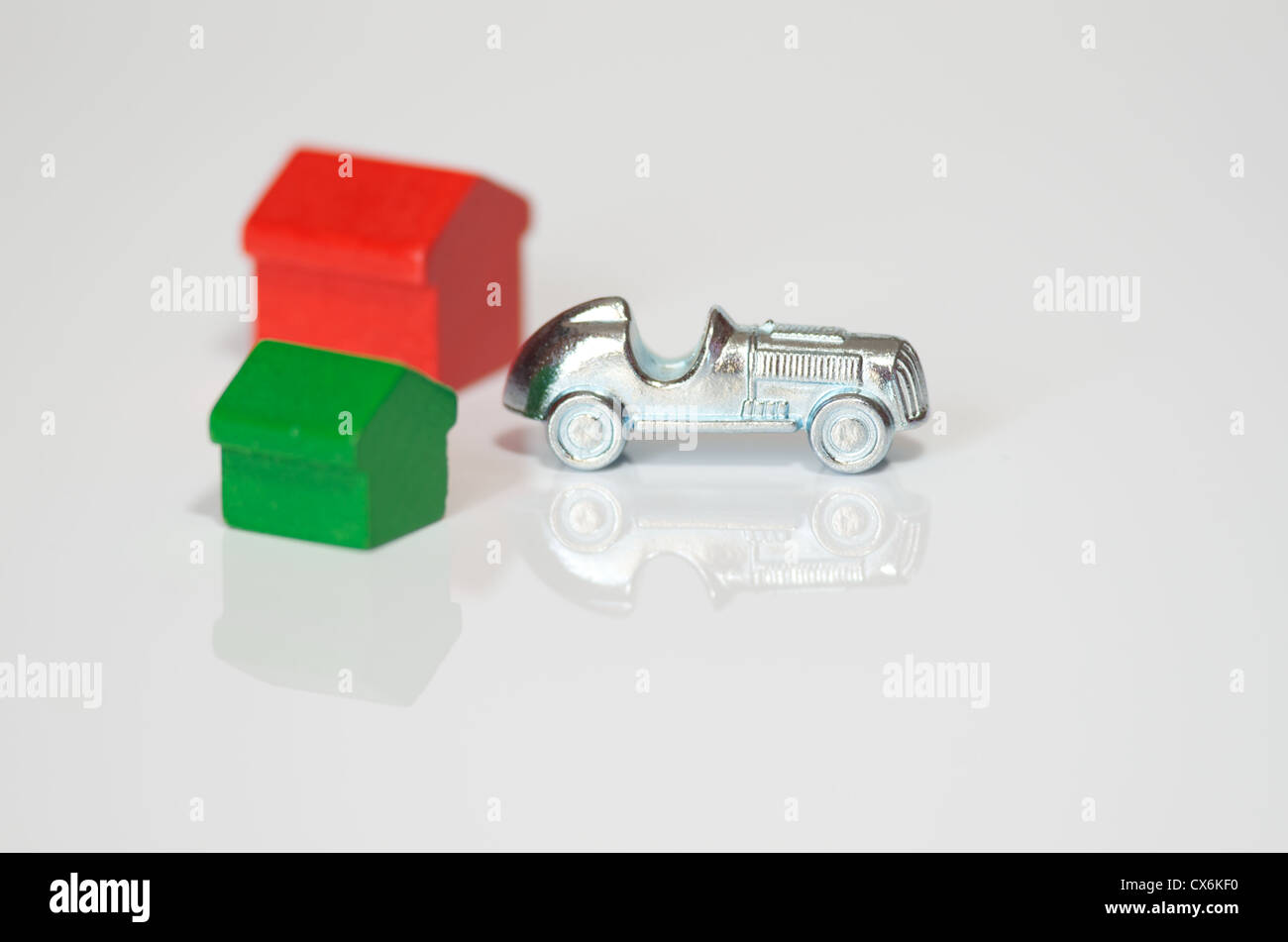 Monopoly car and house isolated on white background with reflection - Stock Image