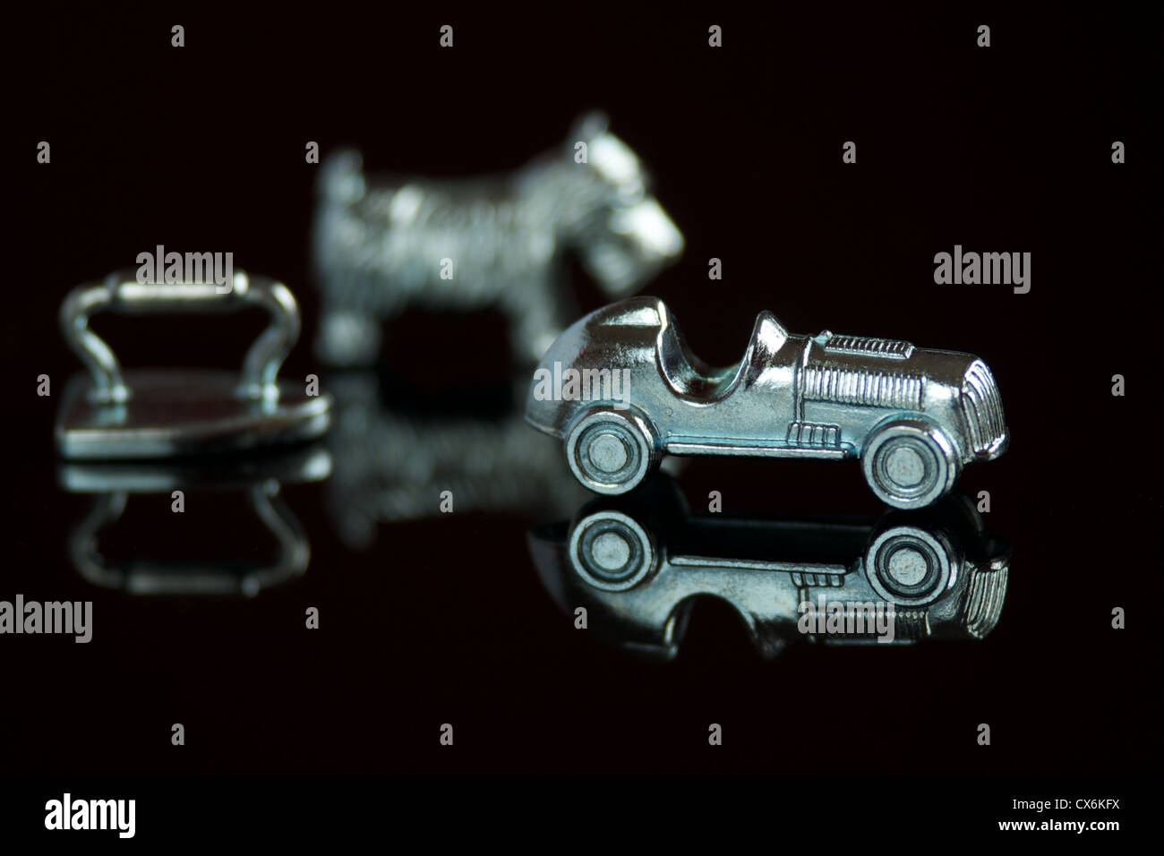 Monopoly game pieces with reflections isolated on a black background - Stock Image