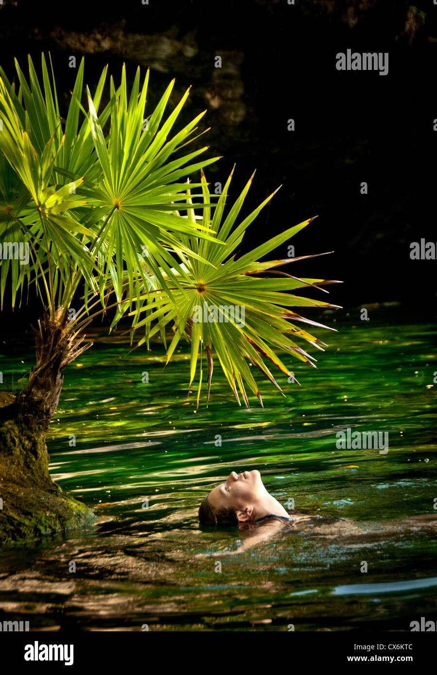 Woman enjoying the water under a fan palm of the Chac Mool Centote in one of the cave systems the Riviera Maya, - Stock Image