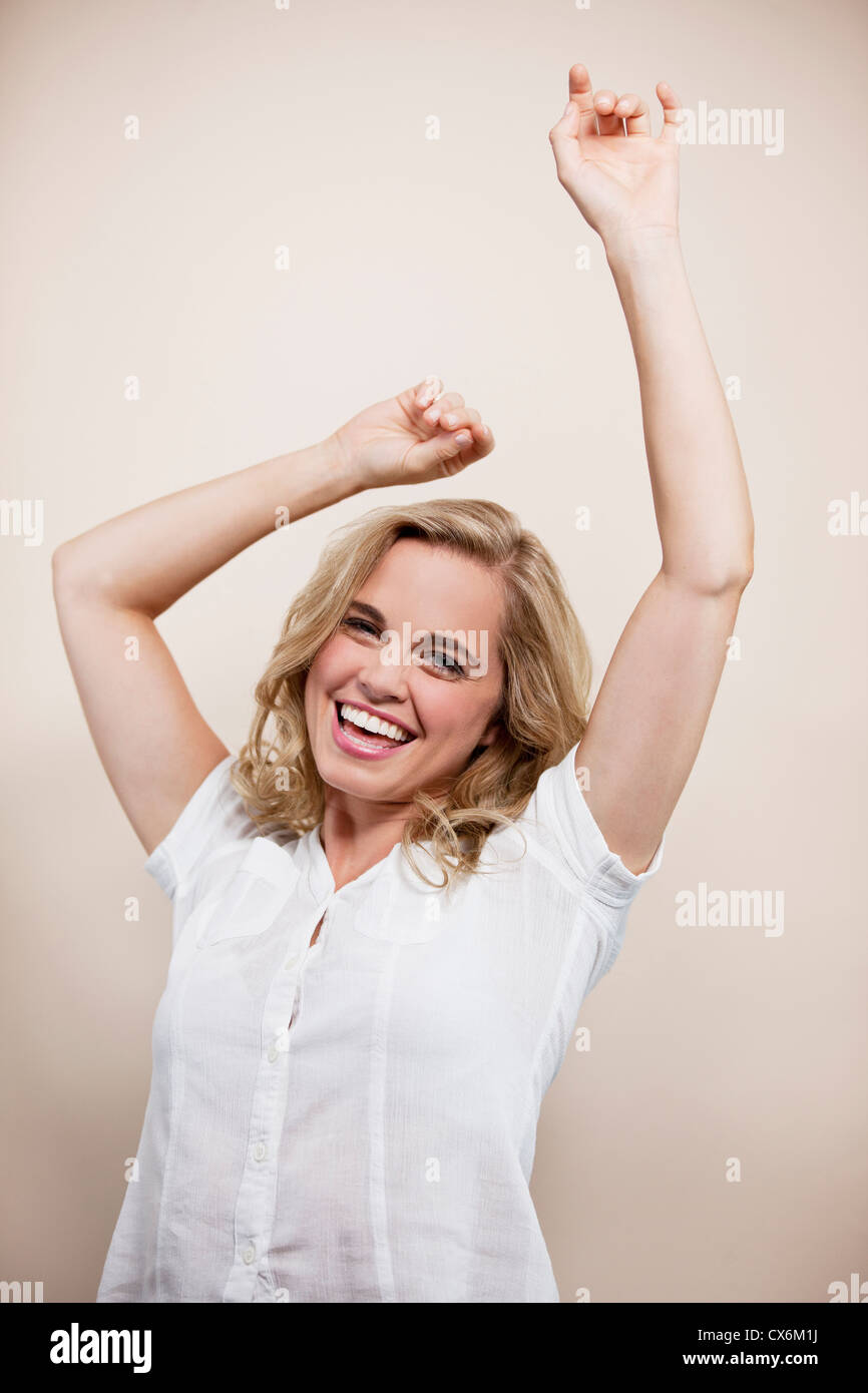 A young blonde woman, arms raised in the air, smiling - Stock Image