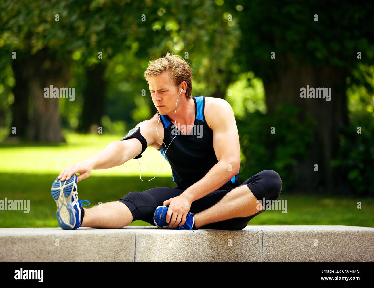 Runner warming up and stretching his legs before running - Stock Image