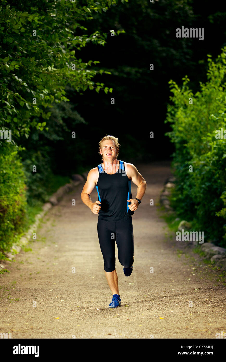 Young athletic man in sportswear running - Stock Image