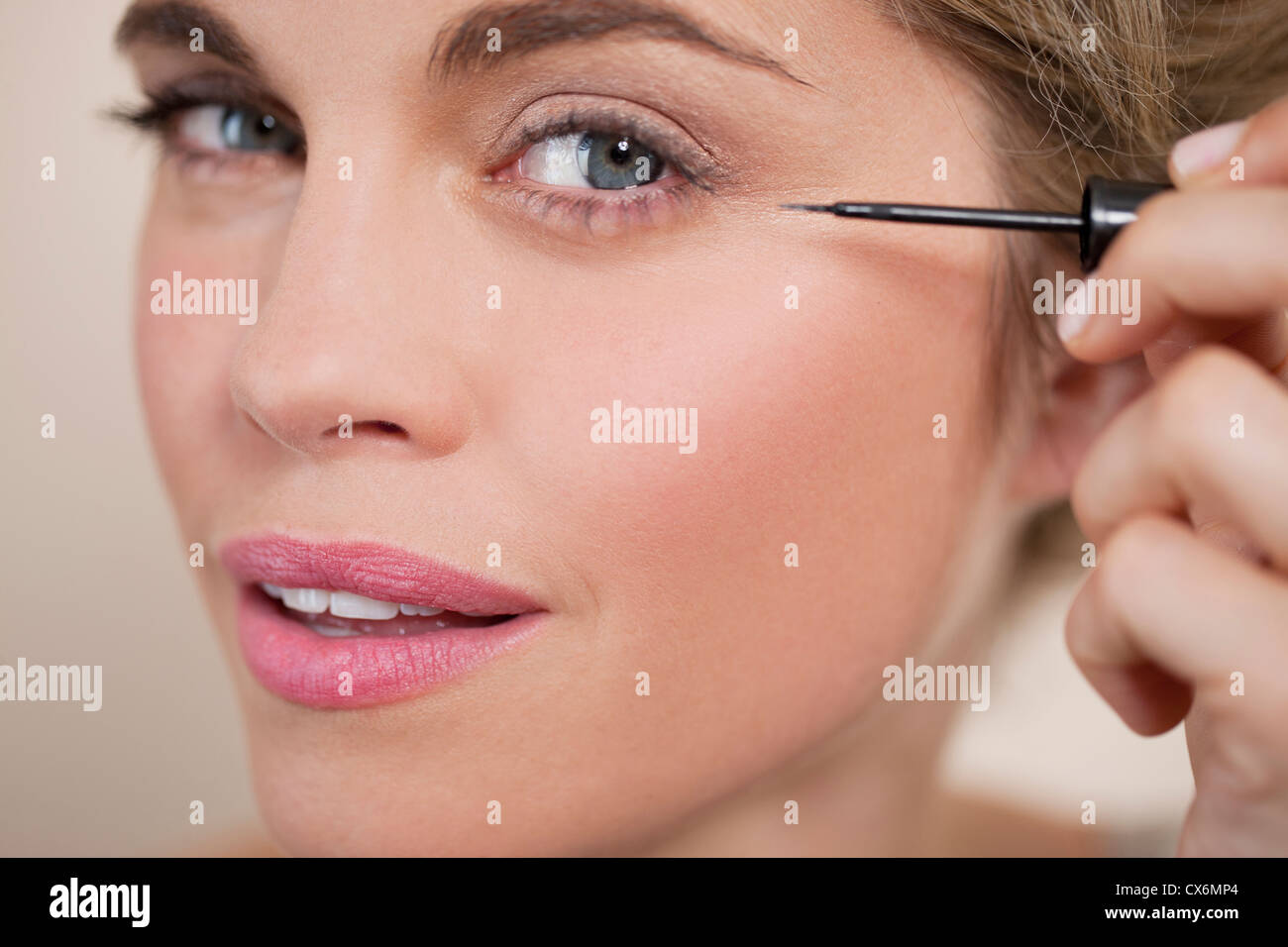A young woman applying liquid eye liner, close up - Stock Image